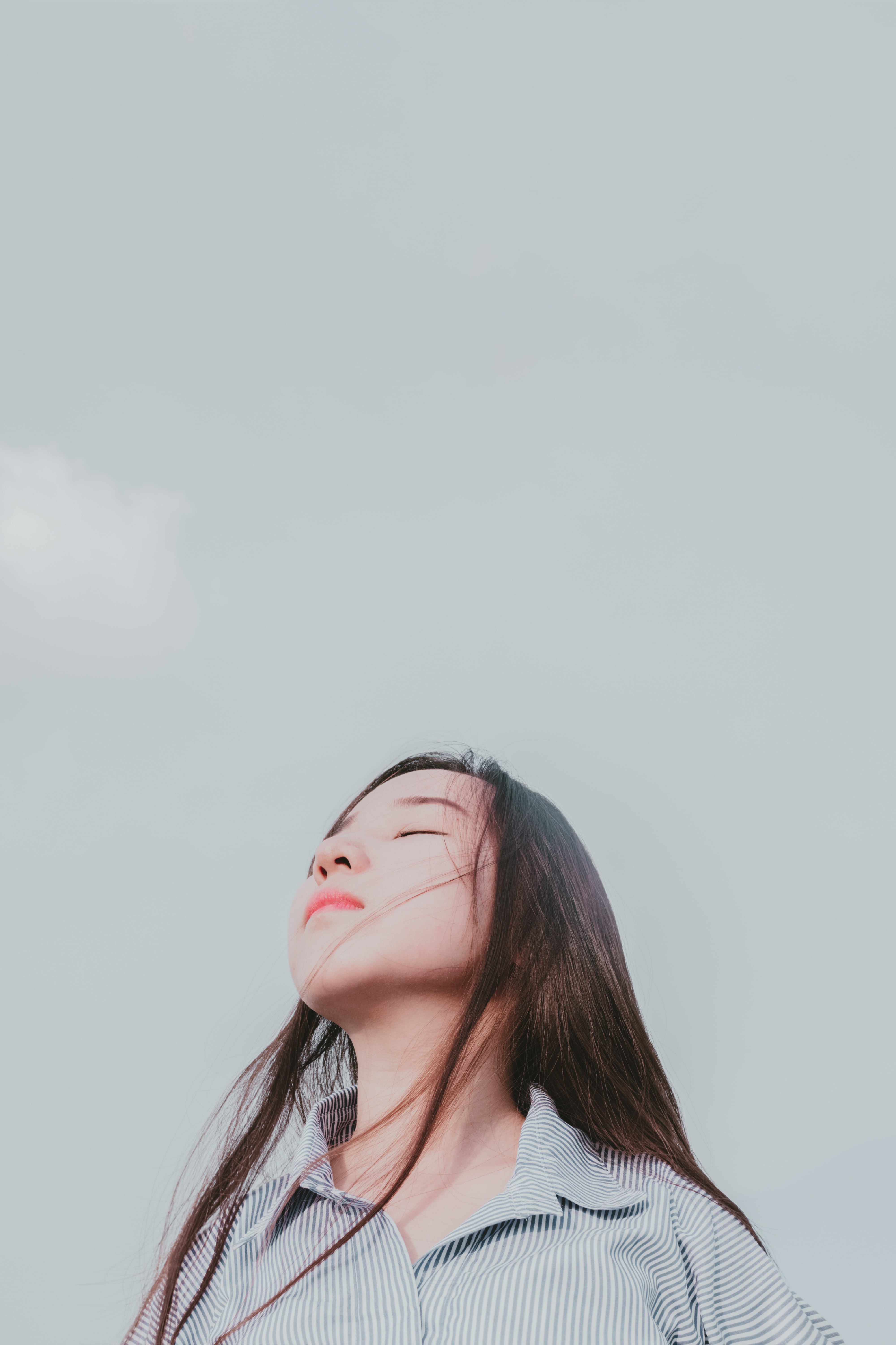 A woman closes her eyes and throws back her head toward the sky