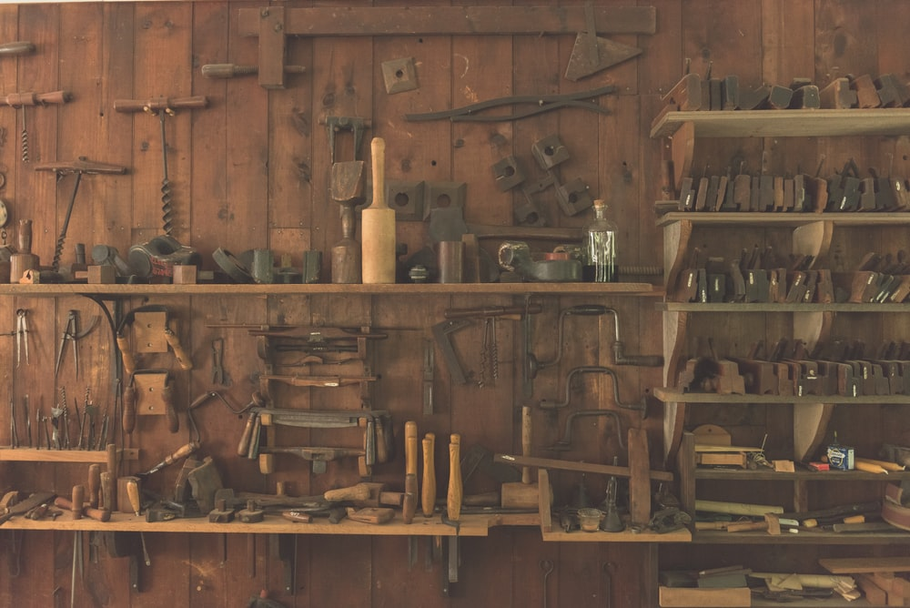 assorted hand tool lot on brown wooden shelf