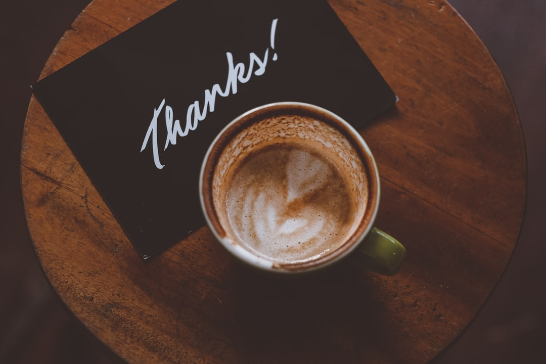 An overhead shot of a thank-you card next to a cup of coffee