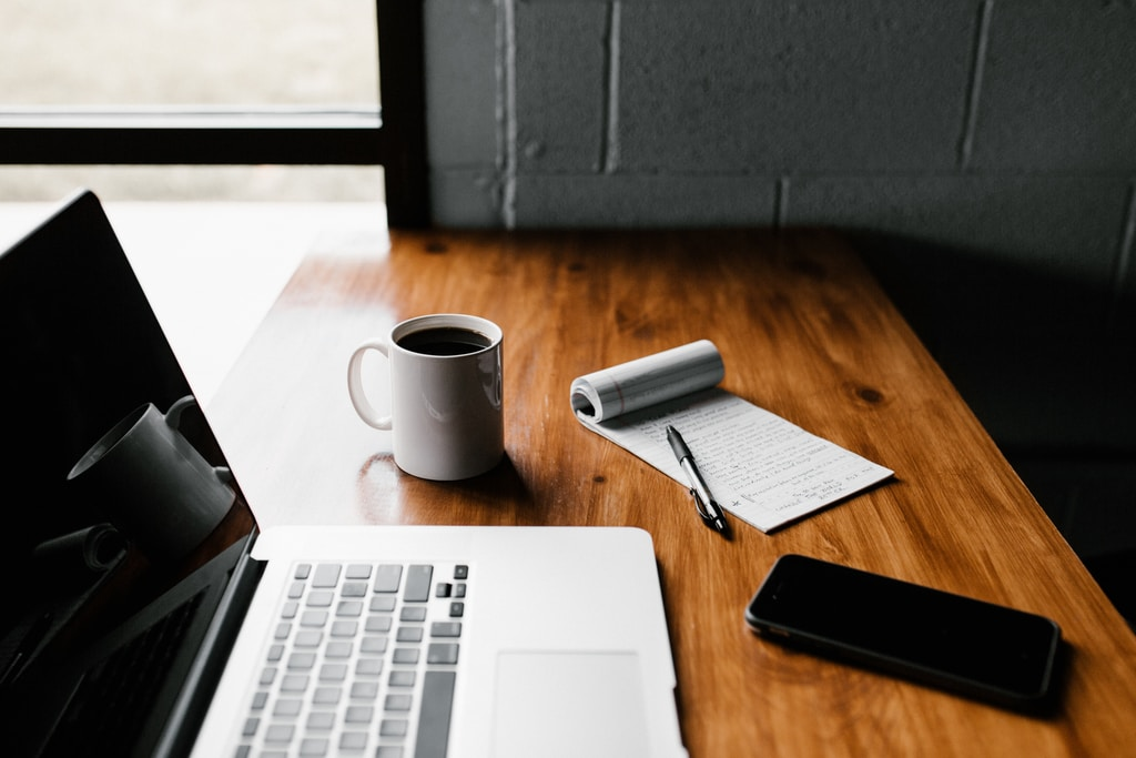 MacBook Pro, white ceramic mug,and black smartphone on table