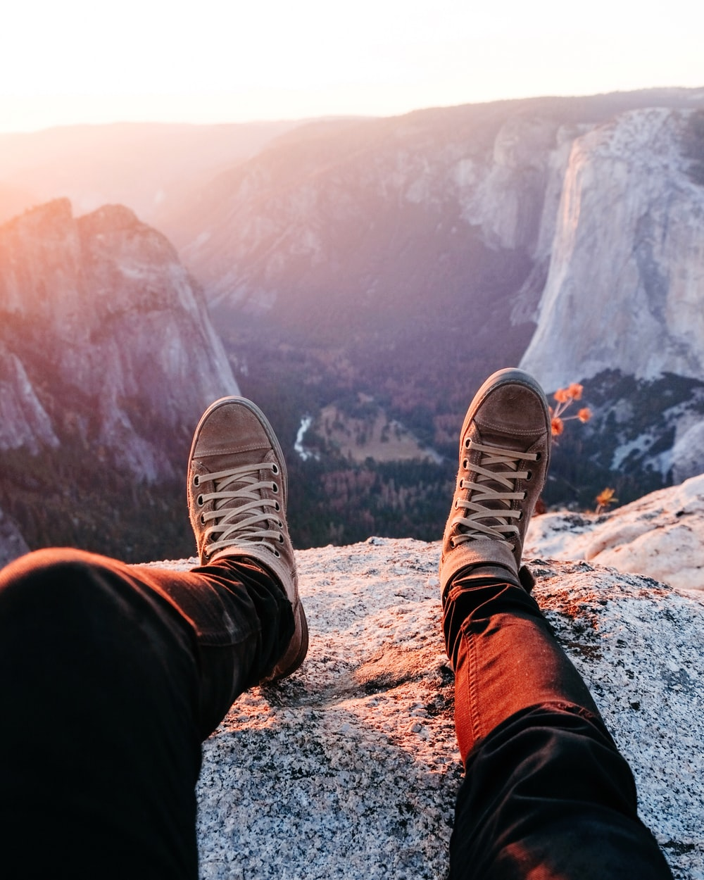 person wearing brown lace-up sneakers sitting on rocky mountain during daytime