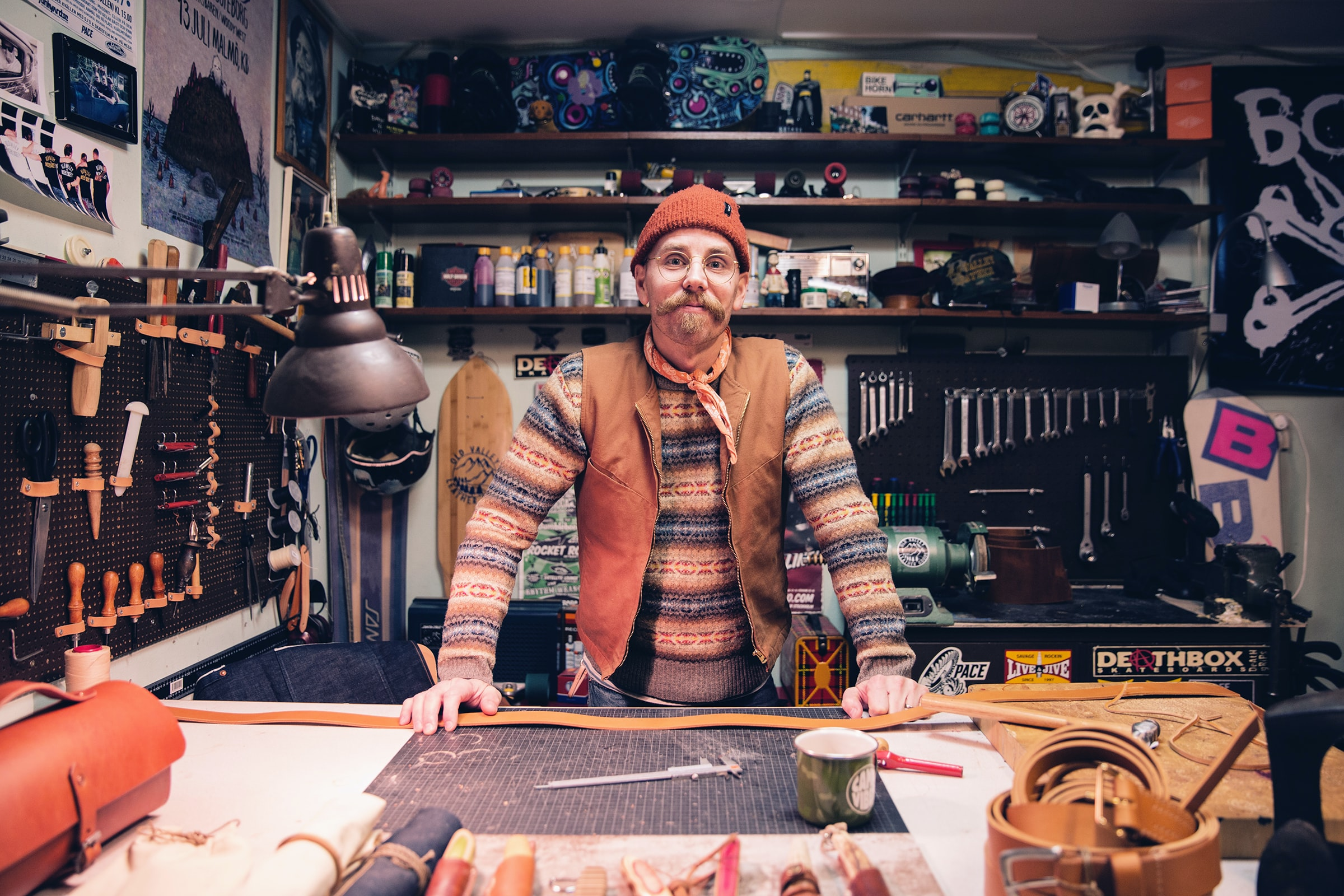 A middle-aged man in a knit cap behind a workbench in a workshop
