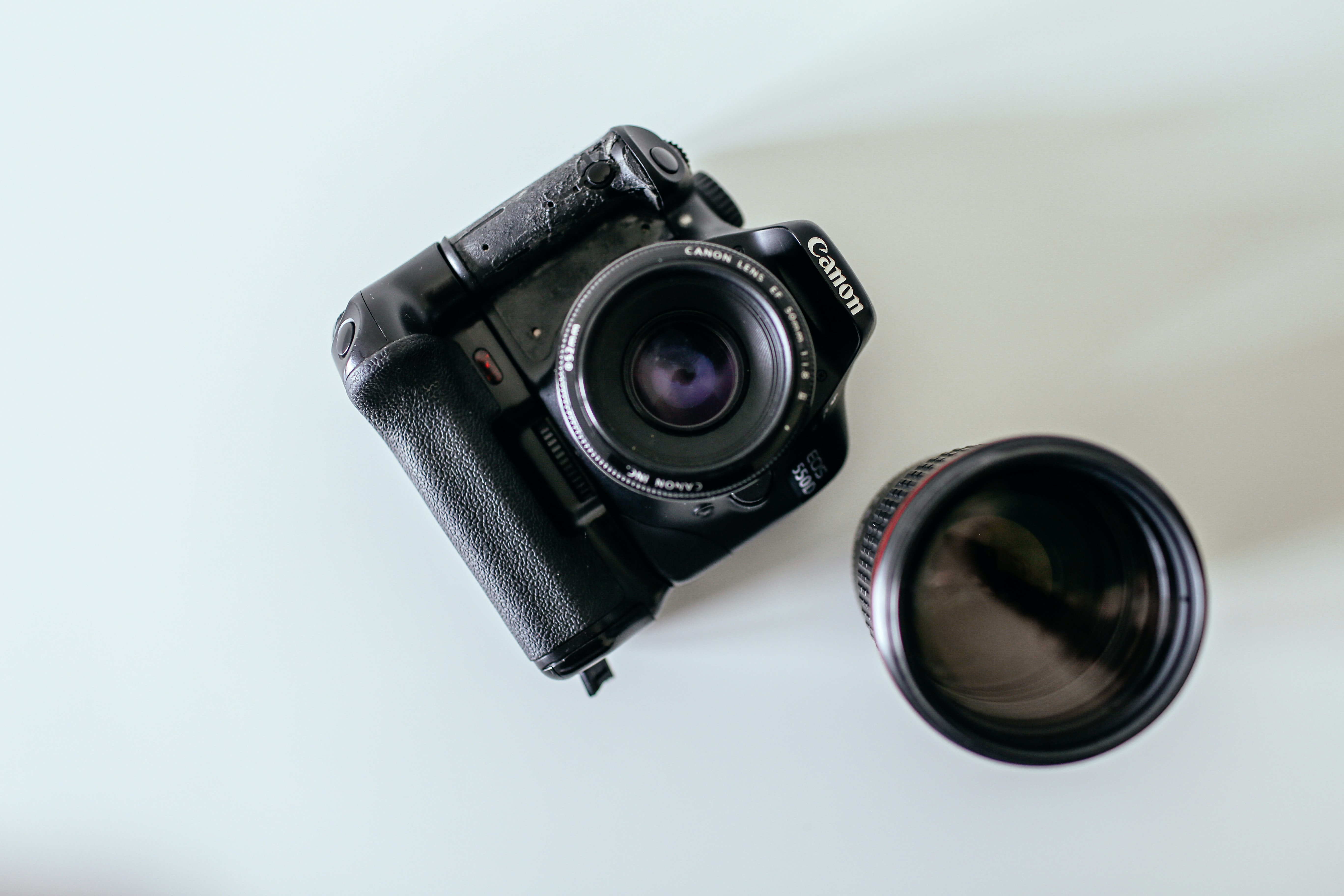 Canon EOS 550D camera on a white surface beside lens