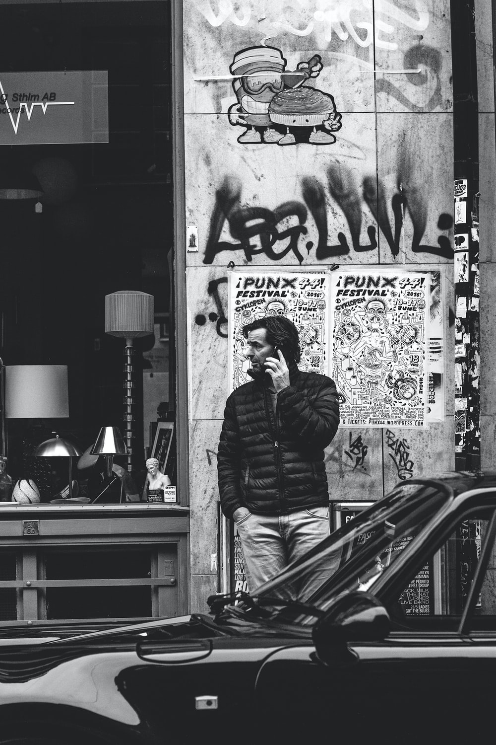 grayscale photography of man using cellphone