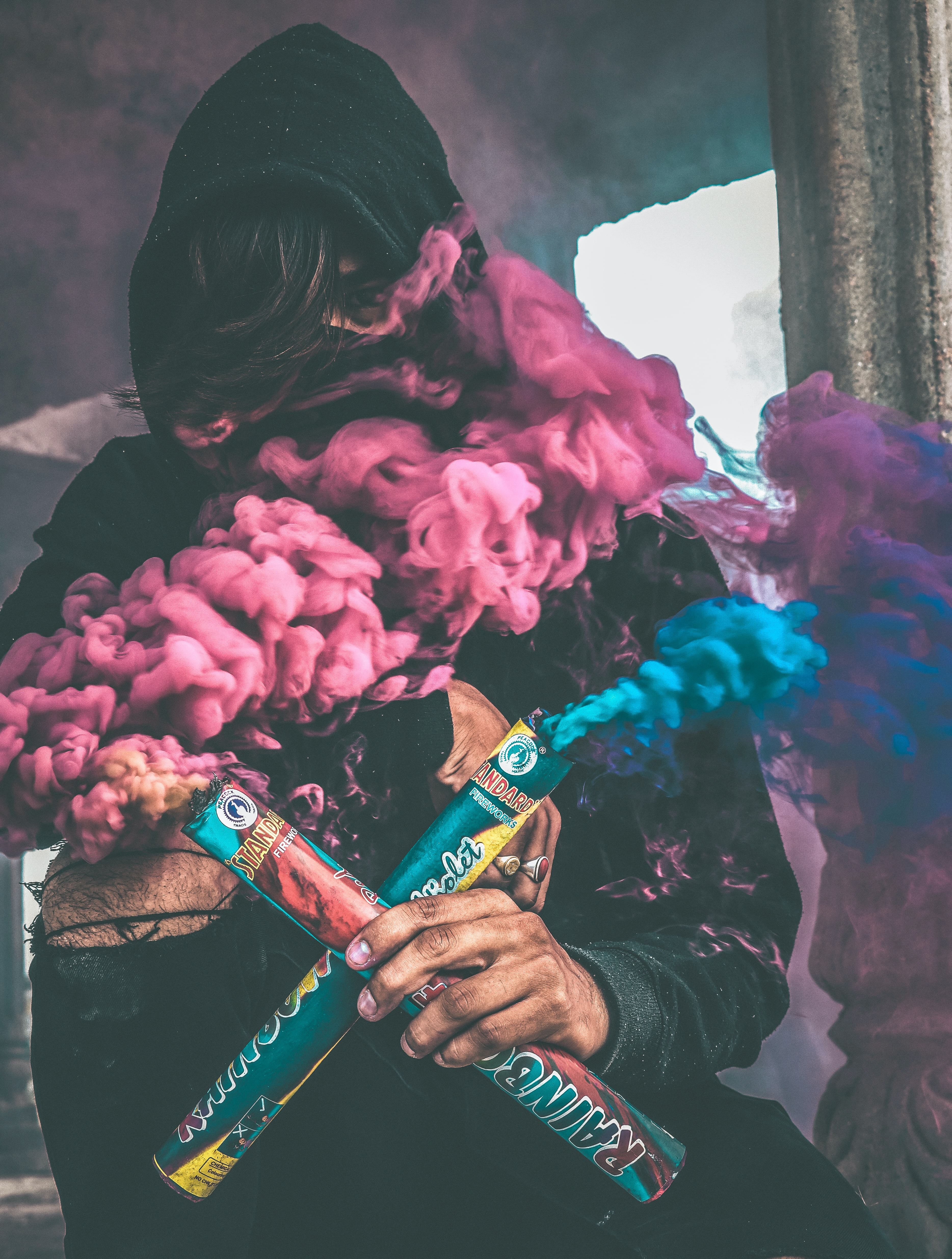 person holding colored smoke