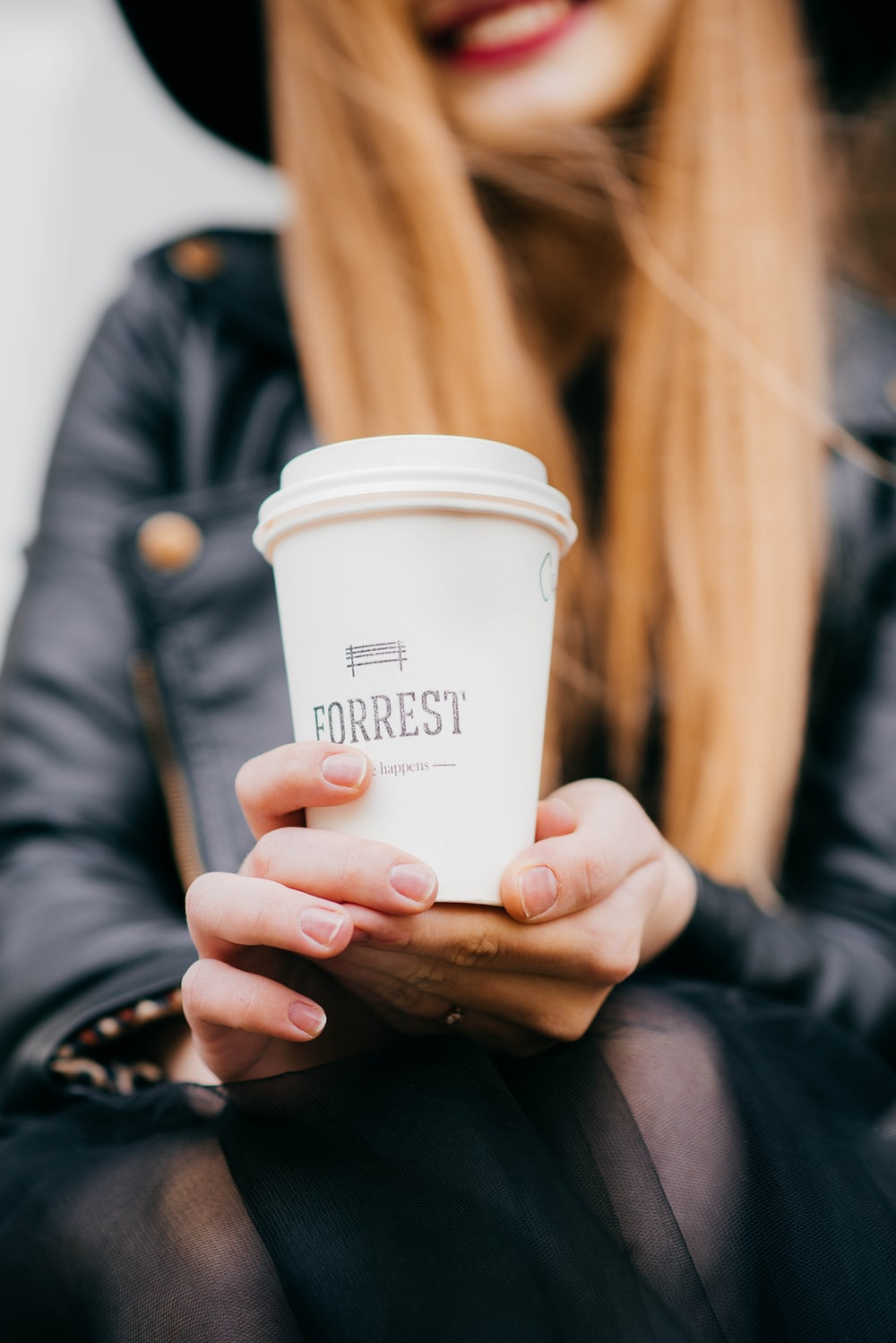 woman holding white Forrest cup with lid selective focus photography