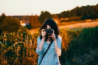 selective focus photography of woman wearing teal and white striped elbow-sleeved blouse