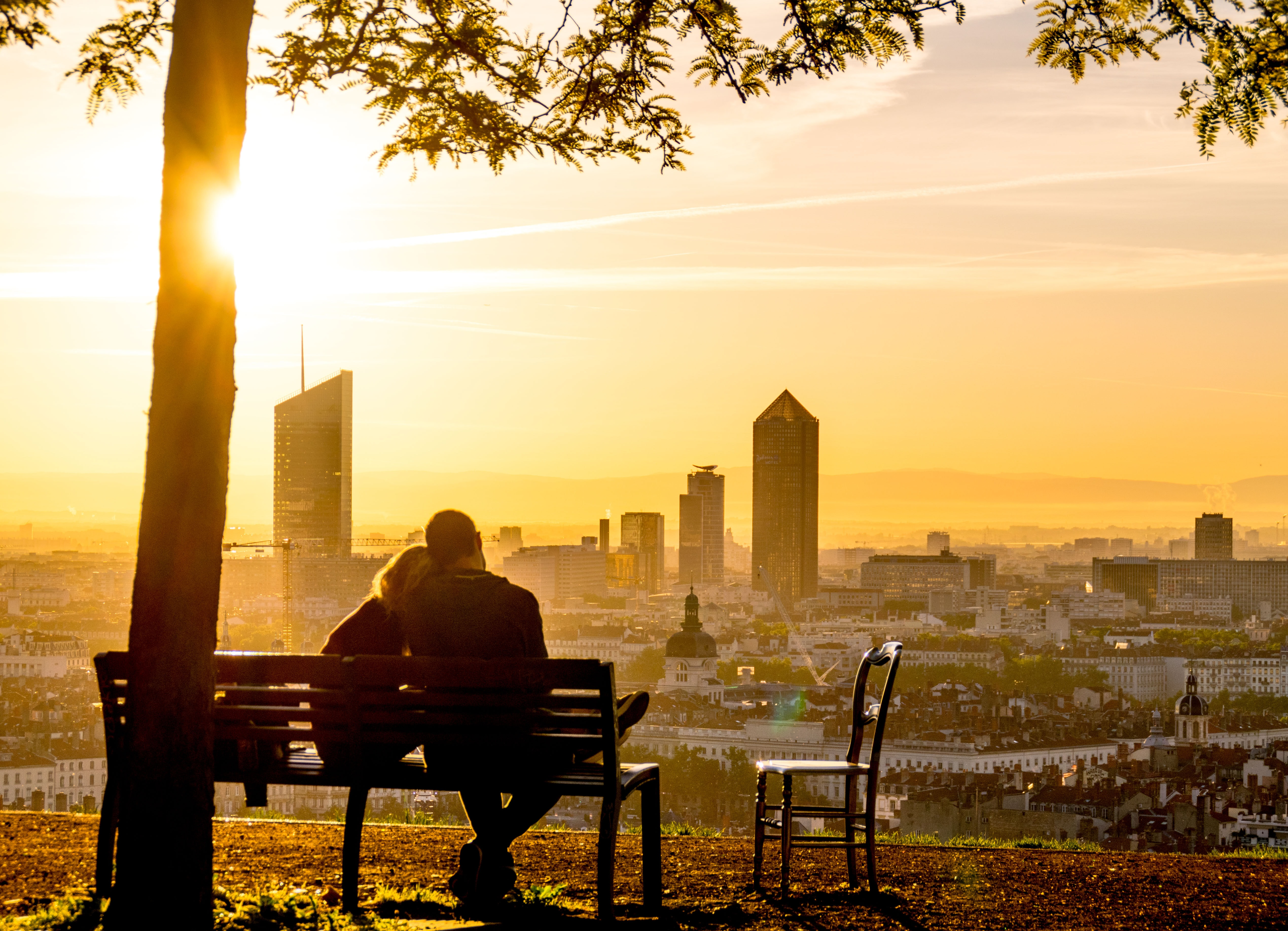 A couple sitting on a park bench while looking down at a city in France.