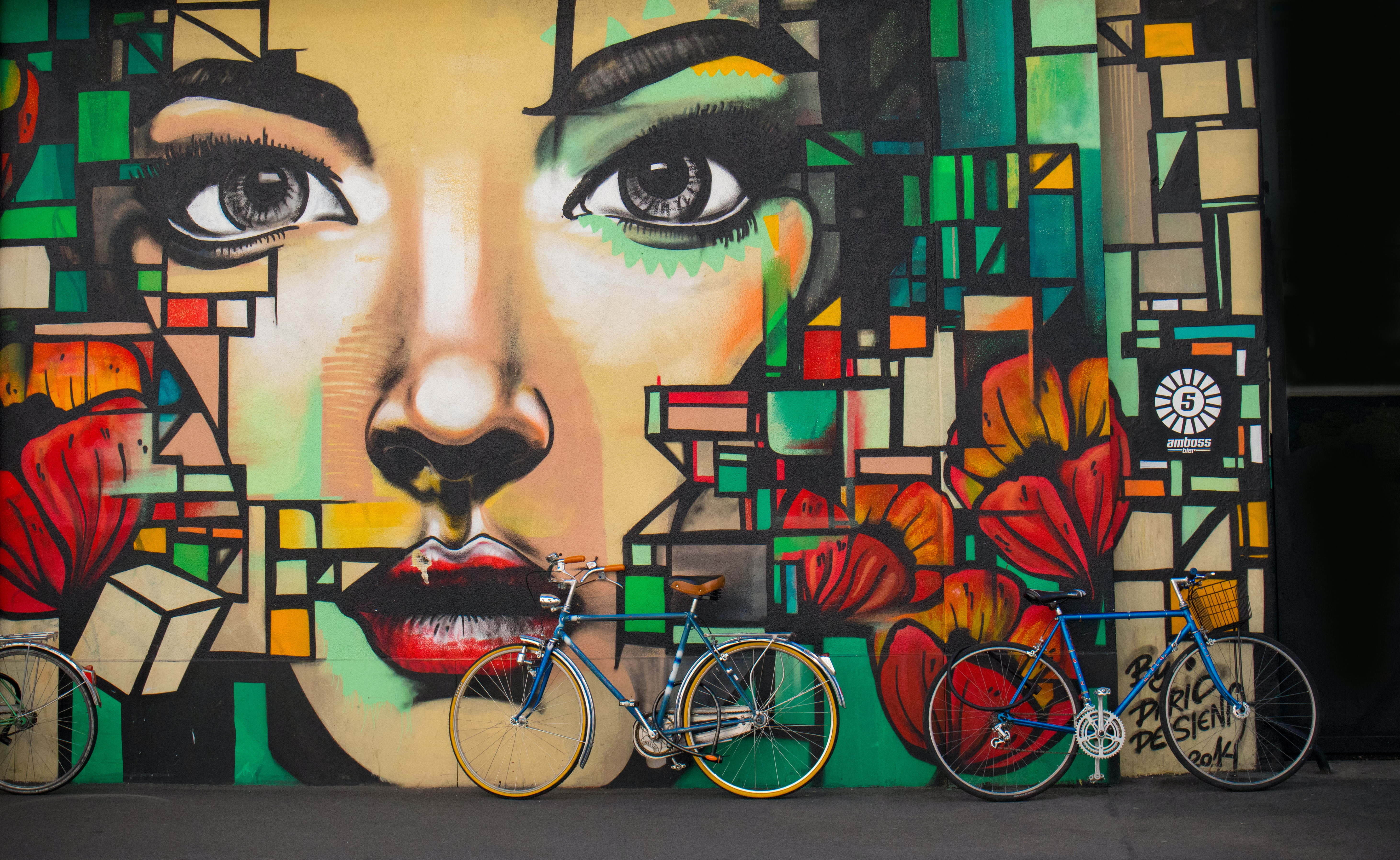 Large colorful graffiti mural of female face and cubism design on wall with bikes in Zürich