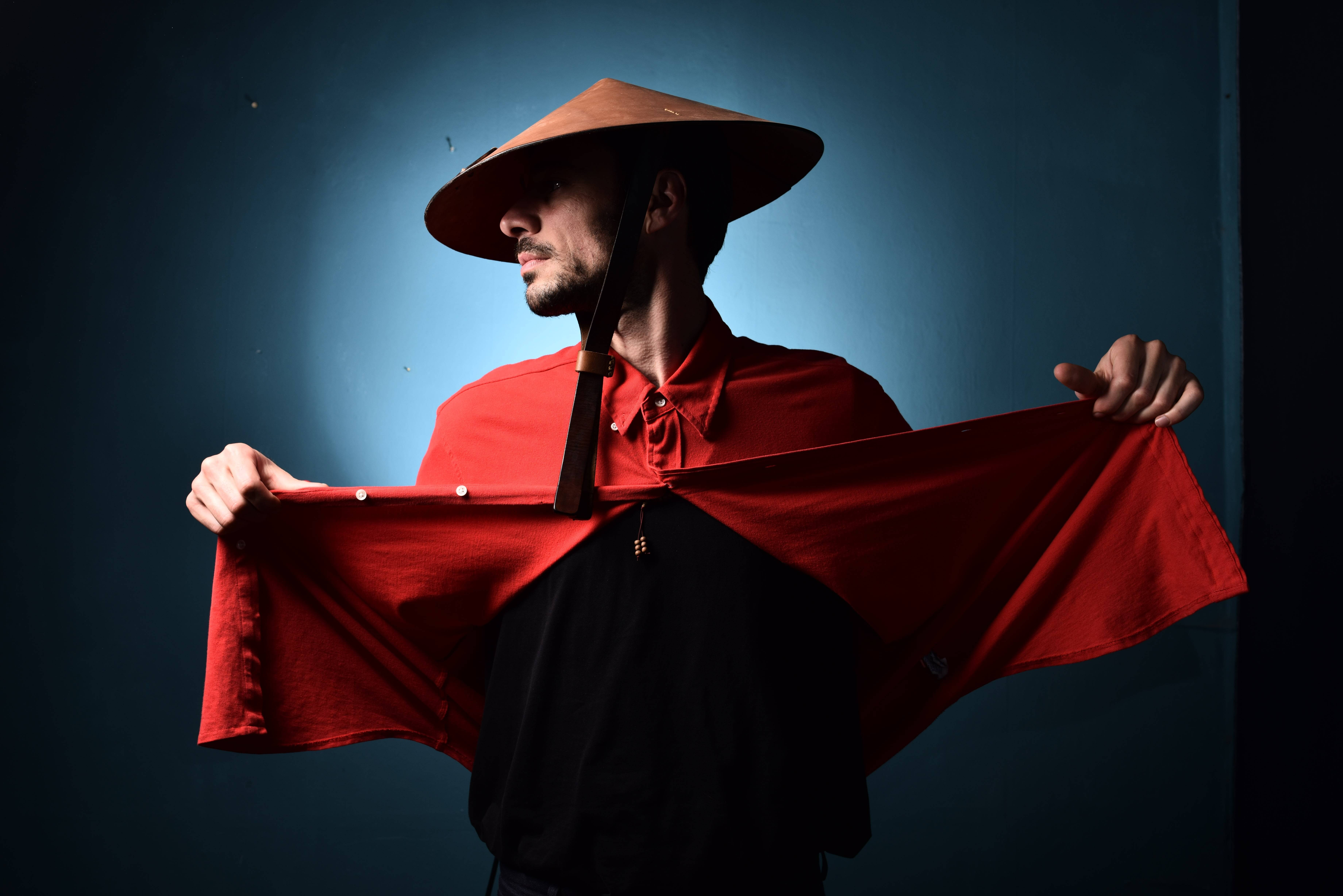 A man is modeling in an Asian conical hat and a red shirt in Yerevan.