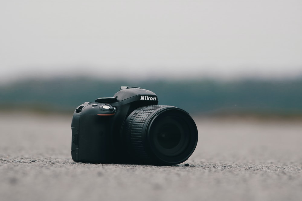 selective focus photography of black Nikon DSLR camera on concrete surface