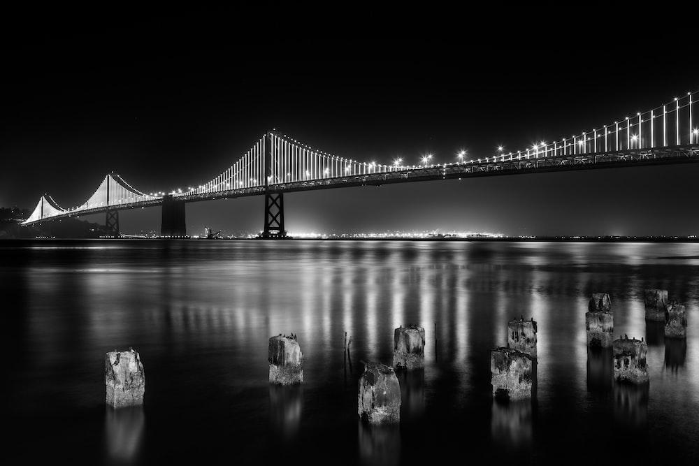 grayscale photography of lightened full-suspension bridge
