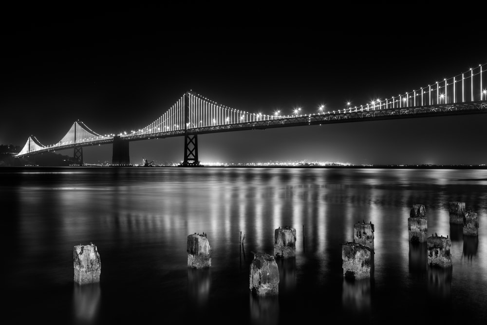 grayscale photography of lightened full-suspension bridge