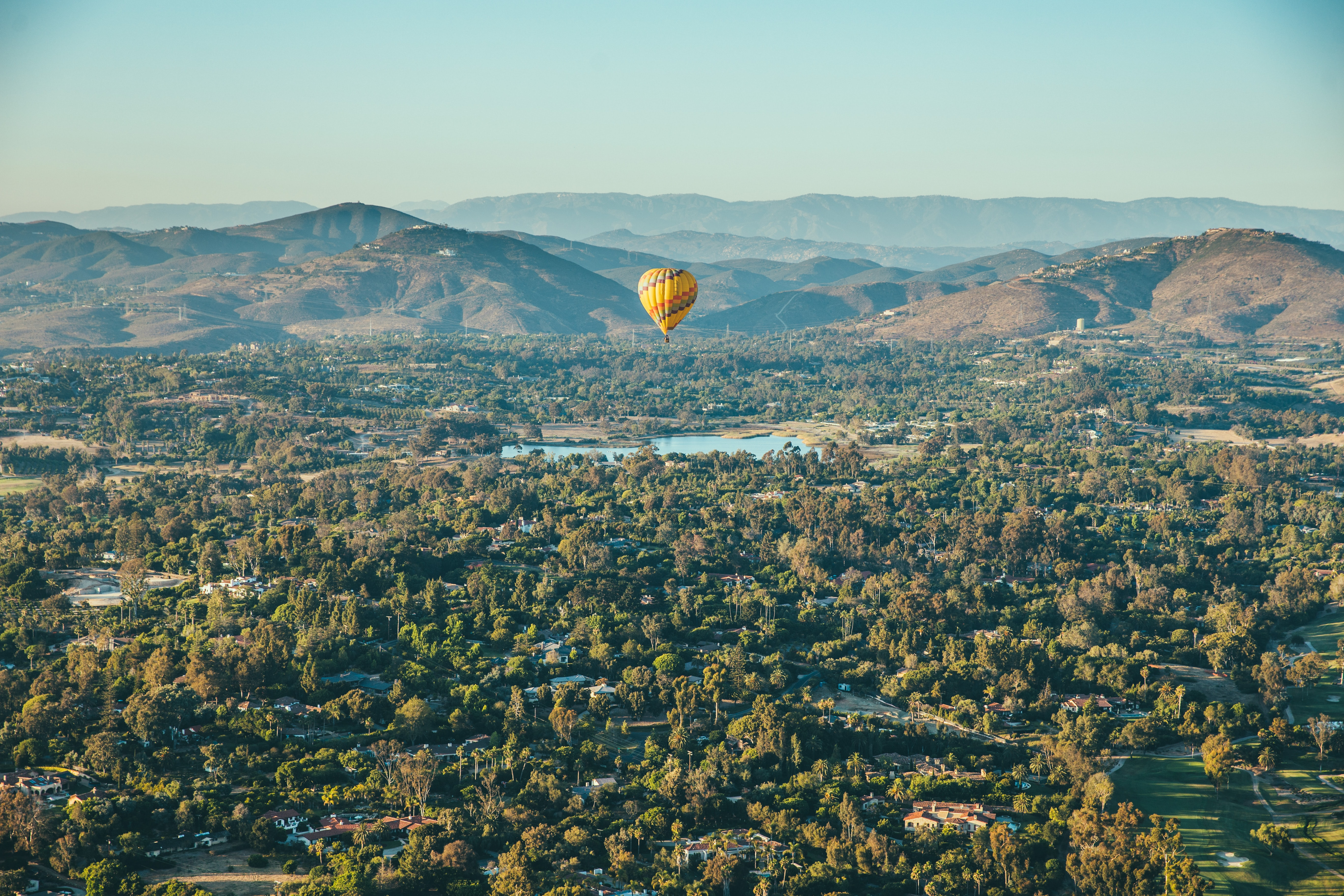 A yellow hot air balloon in the air above a small village among hills