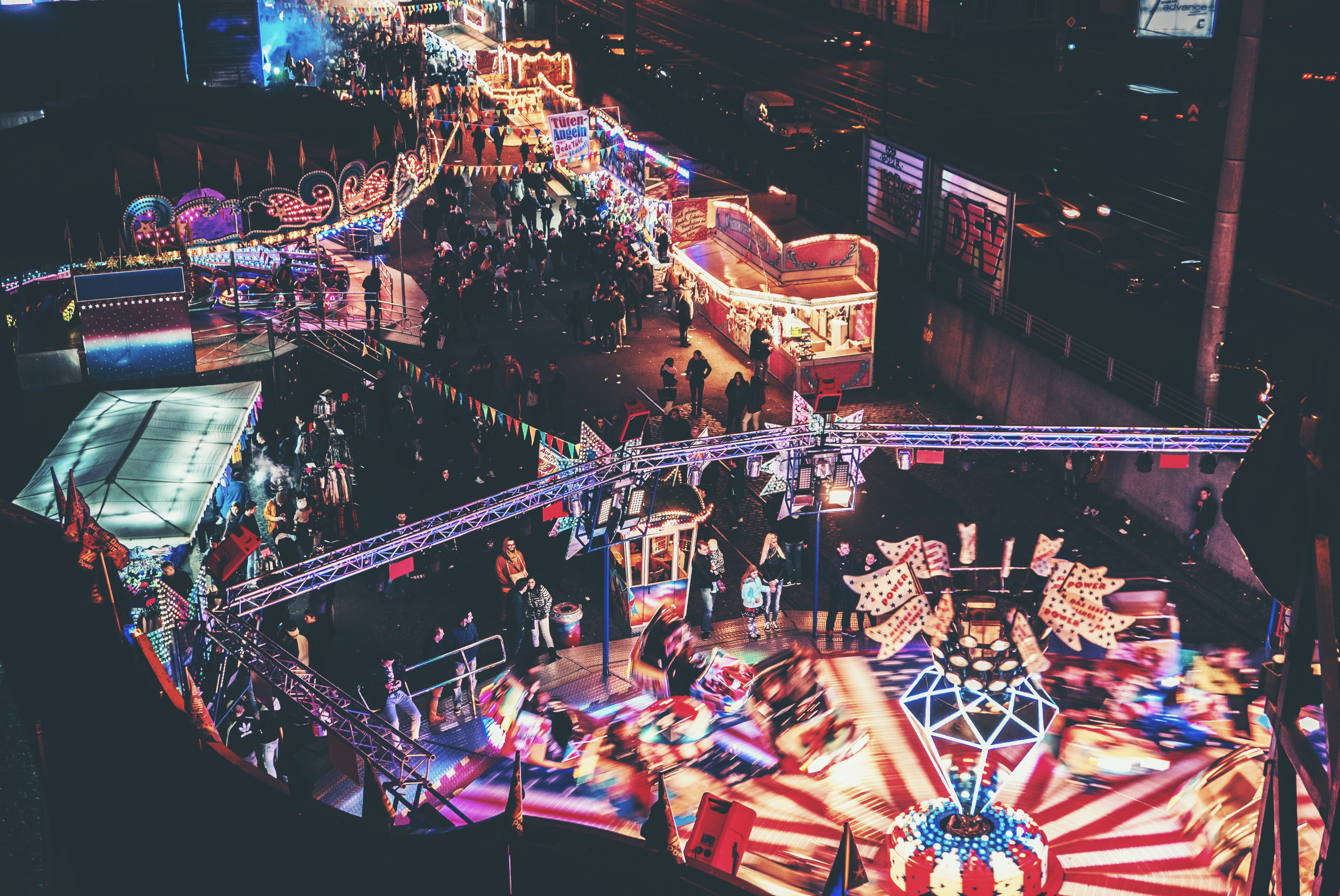Crowd going around a Cologne amusement park with rides and stalls lighting up the night