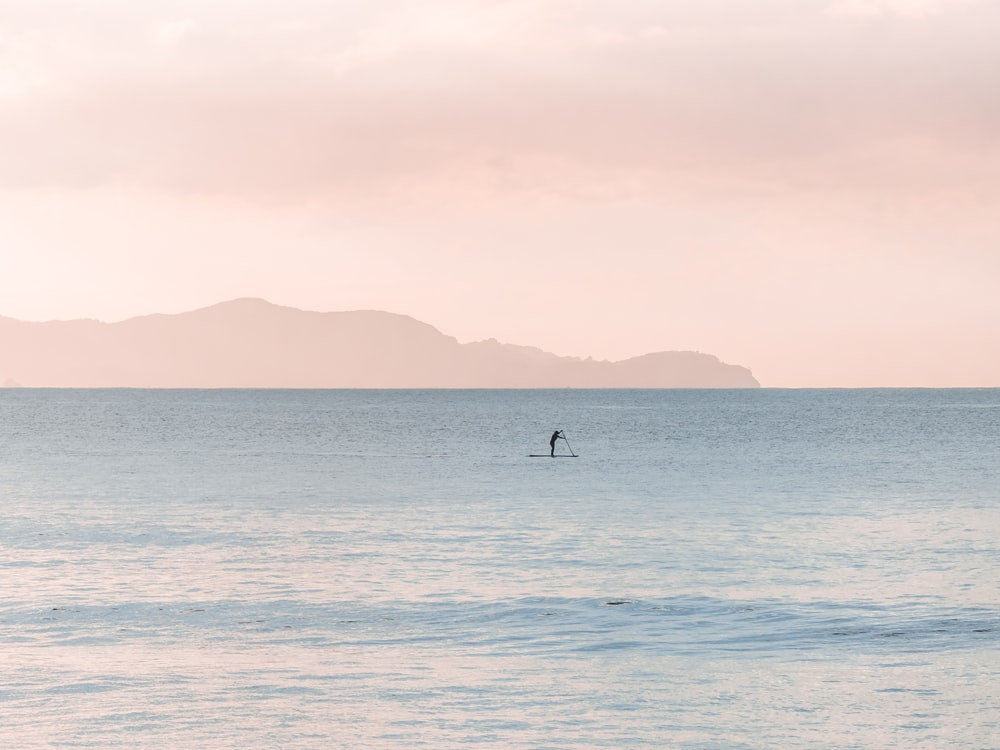 person paddle boarding during daytime