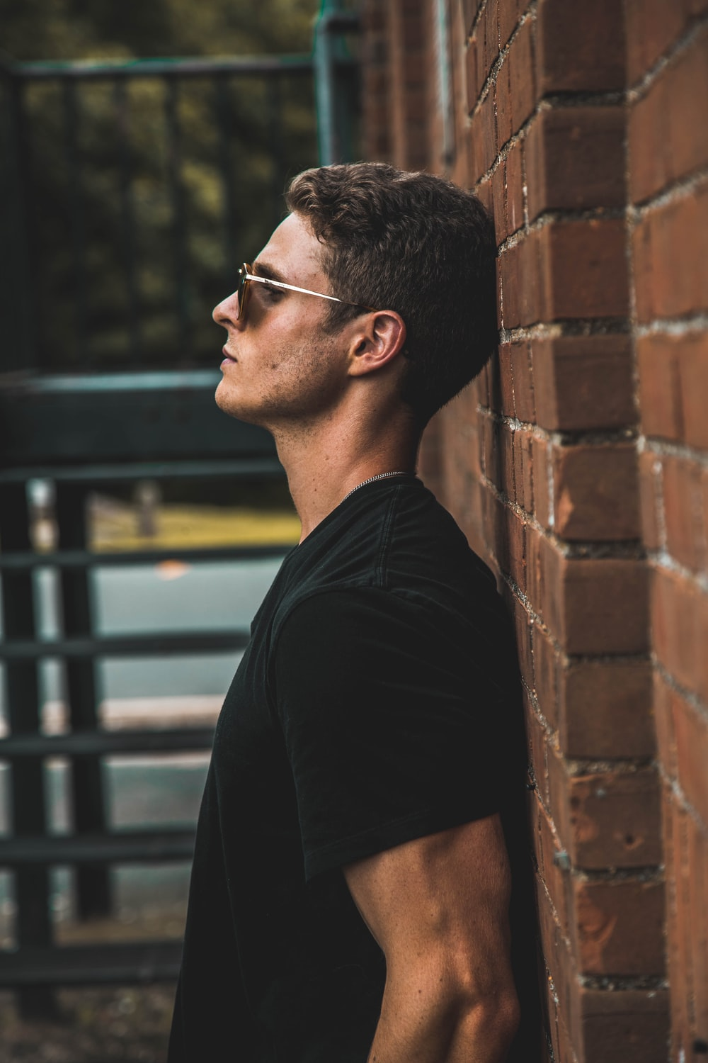 man in black short-sleeved shirt leaning on brow brick wall