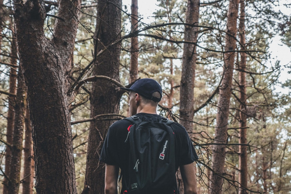 man carrying black backpack on froest