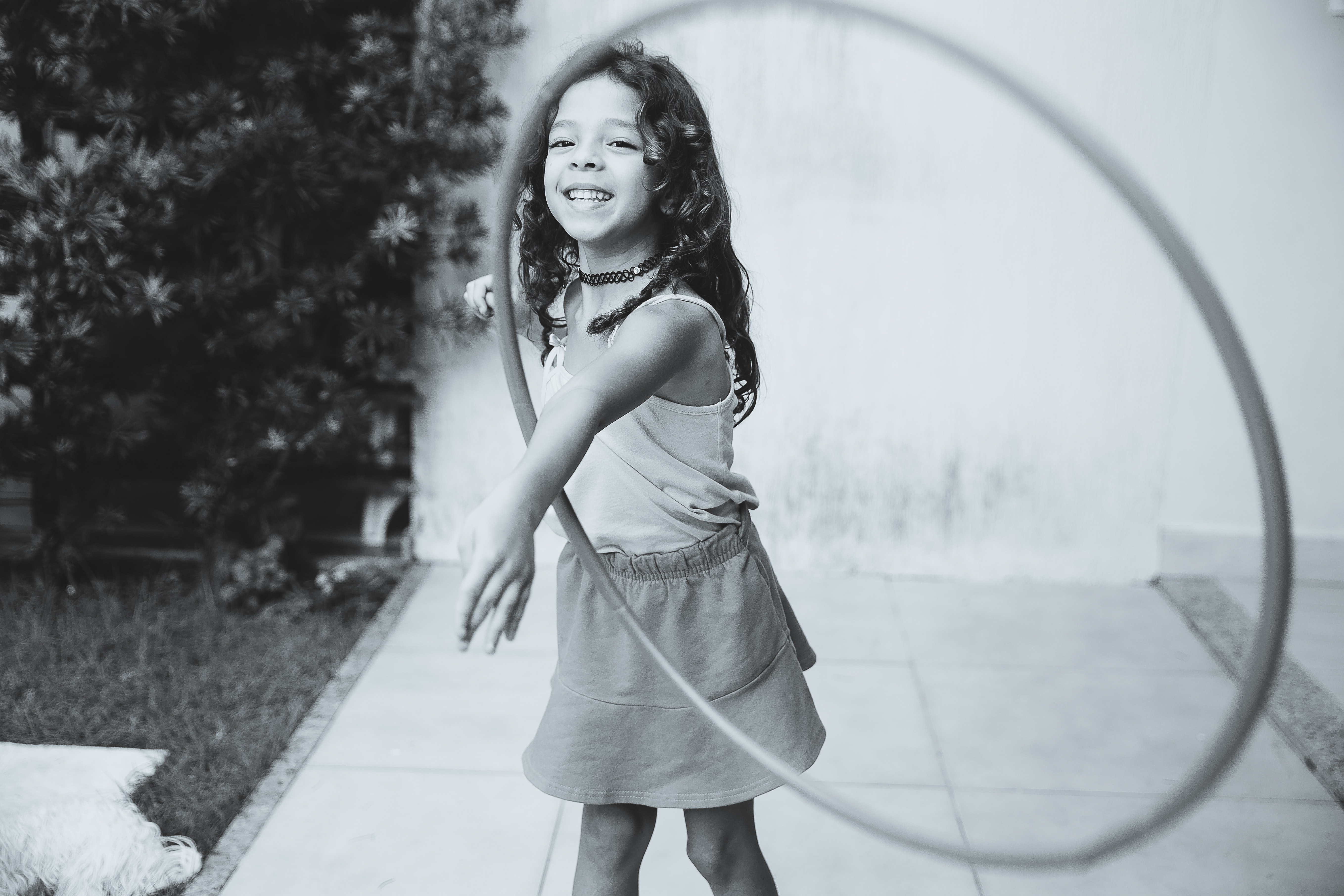 A black-and-white child playing with a hula hoop outdoors in Aracaju
