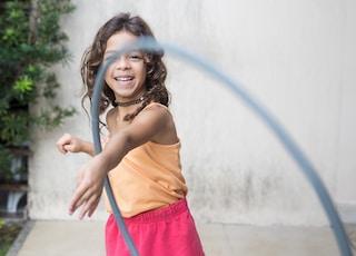 girl playing hula hoop on his arm