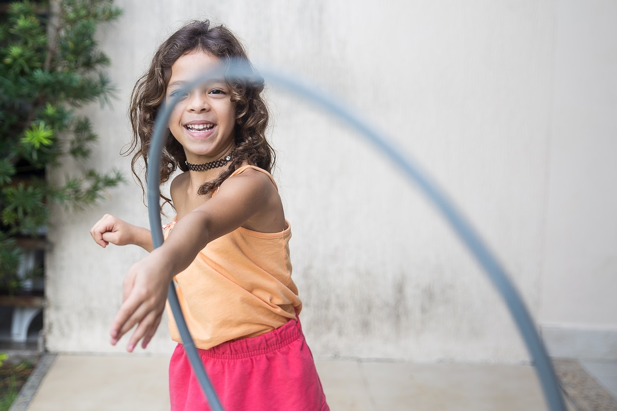 A happy child learning to hula hoop on their arm.