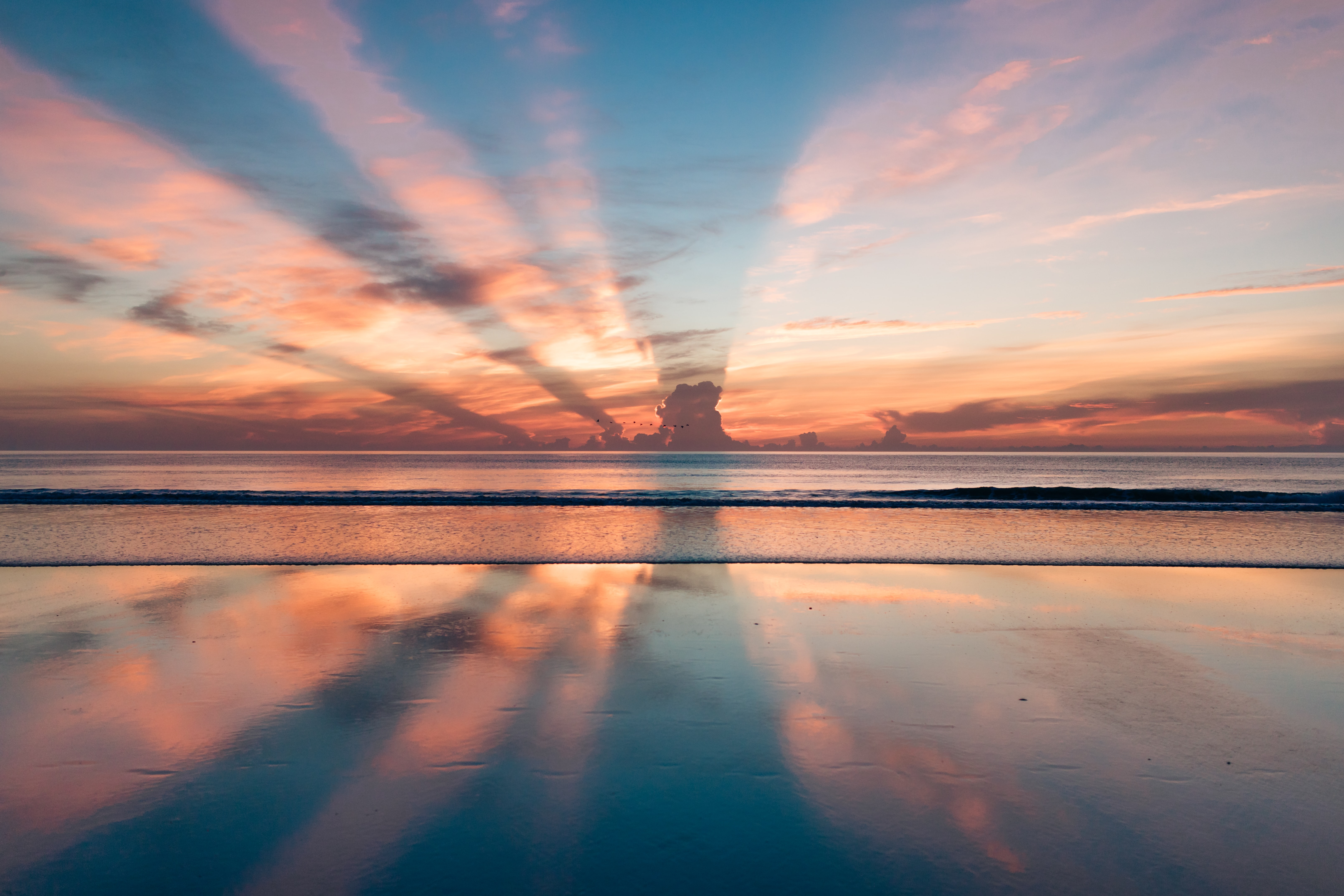 Rays from the sunset burst through the Daytona Beach clouds and reflect perfectly on the calm sea waters