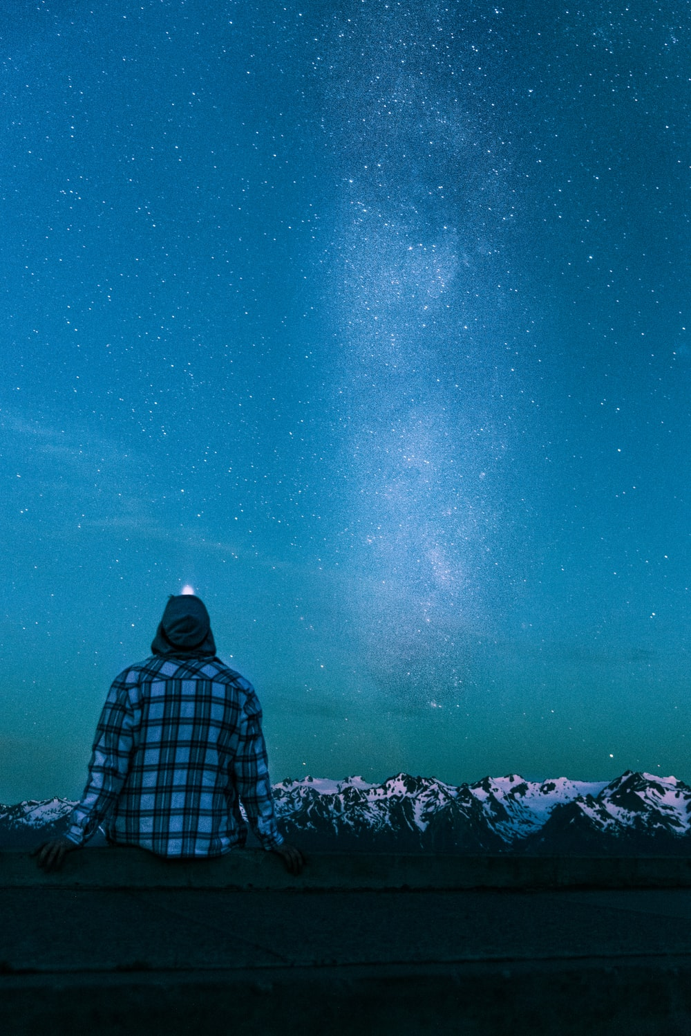 man sitting on gray wall looking at the stars