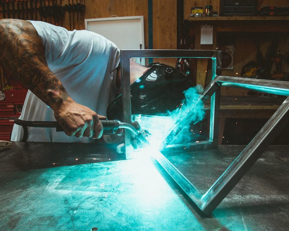 man welding two rectangular gray metal frames