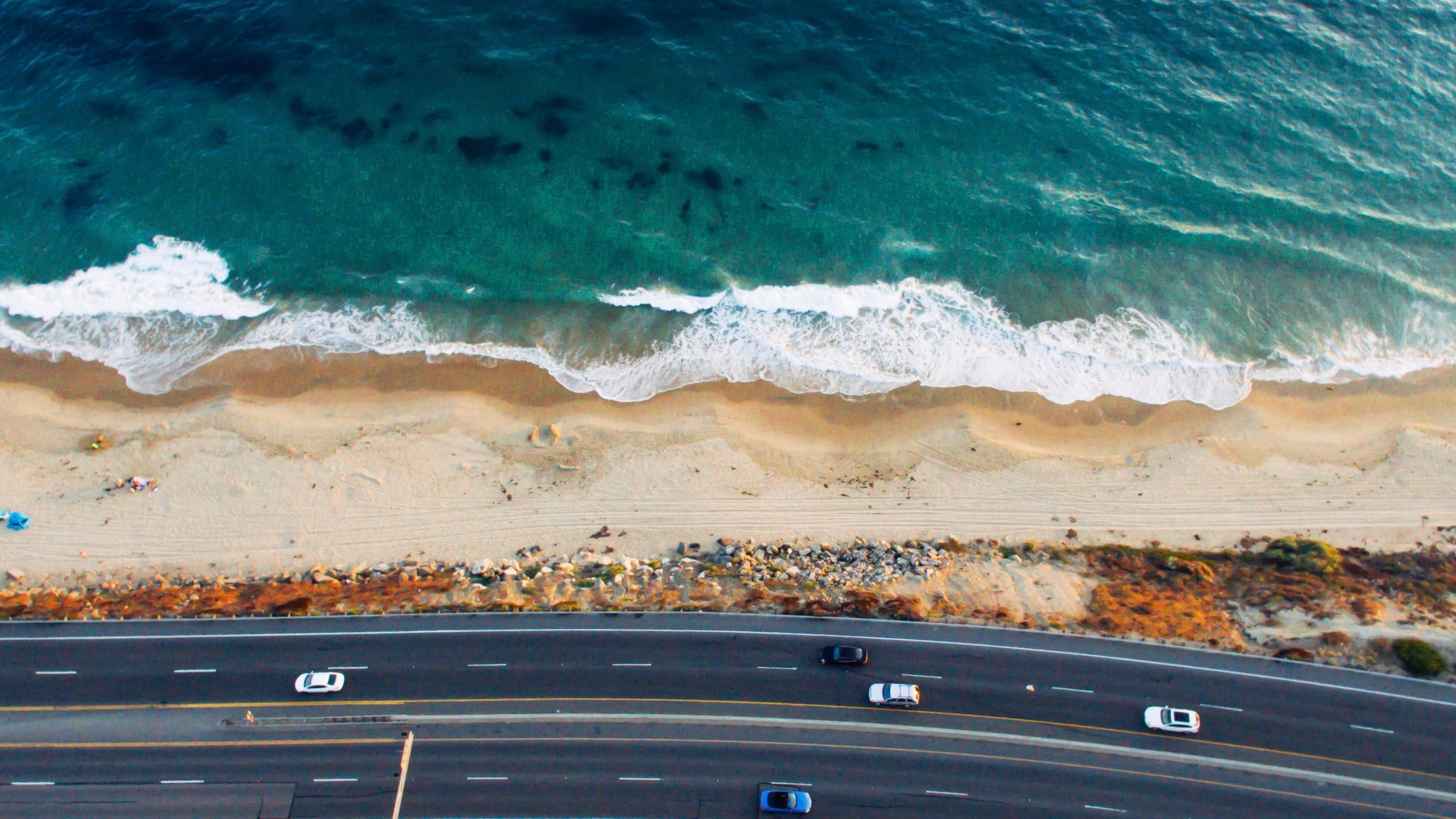 Drone view of a highway with cars by the sandy beach shoreline at Crystal Cove State Park