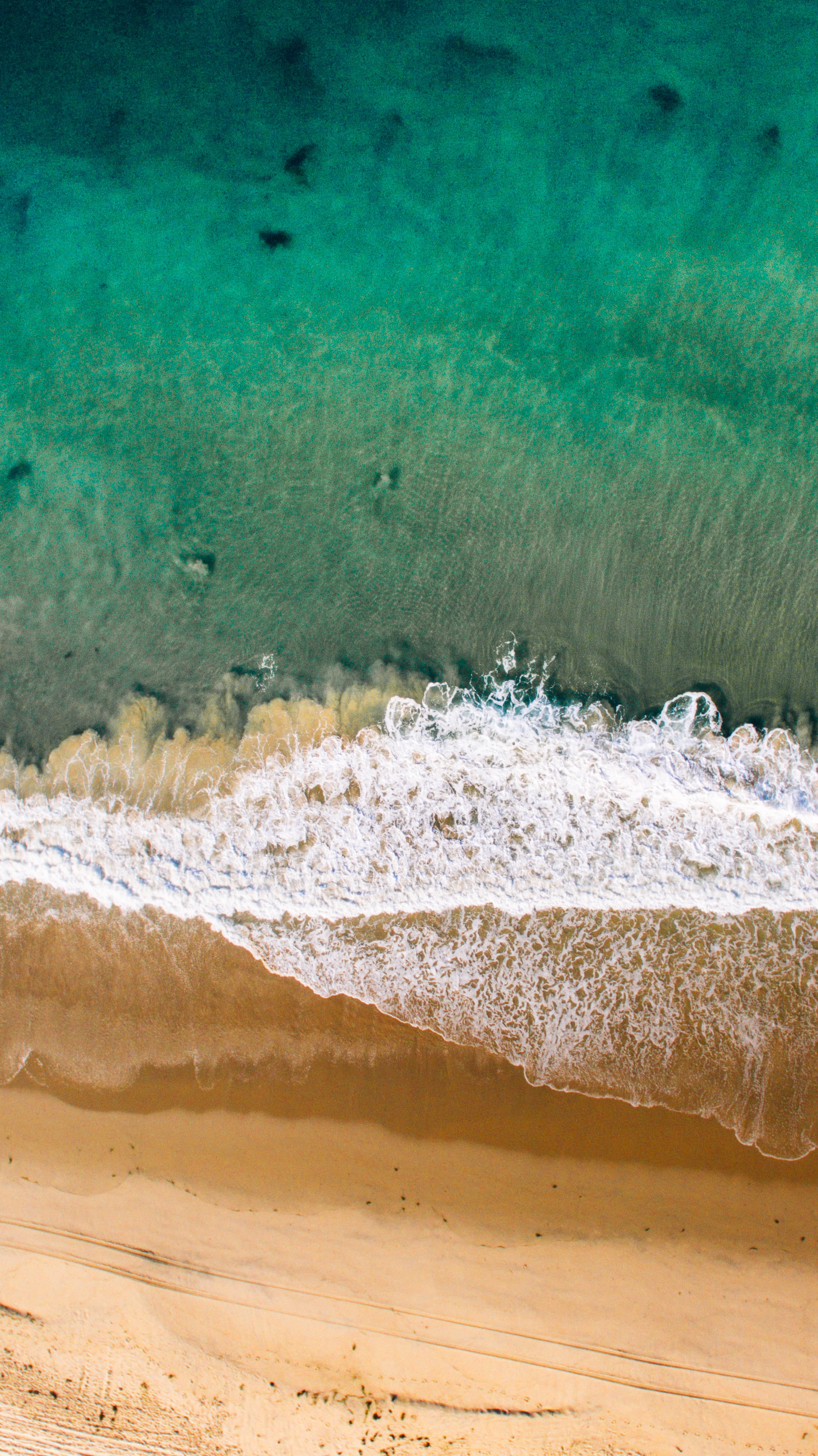 Drone view of the waves crashing on the sand beach shore