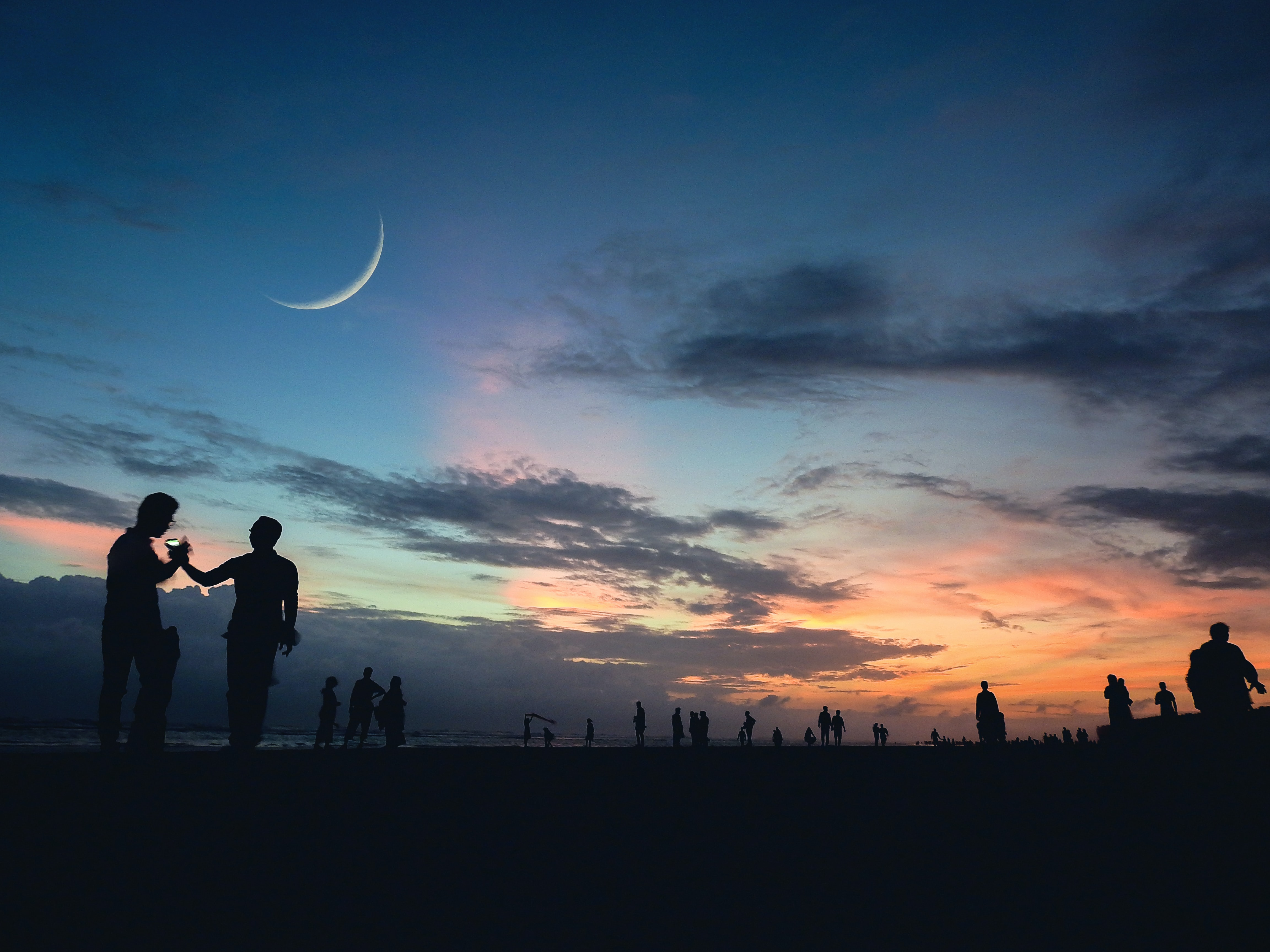 People silhouetted against a twilit sky pinned with a crescent moon at Cox's Bazar