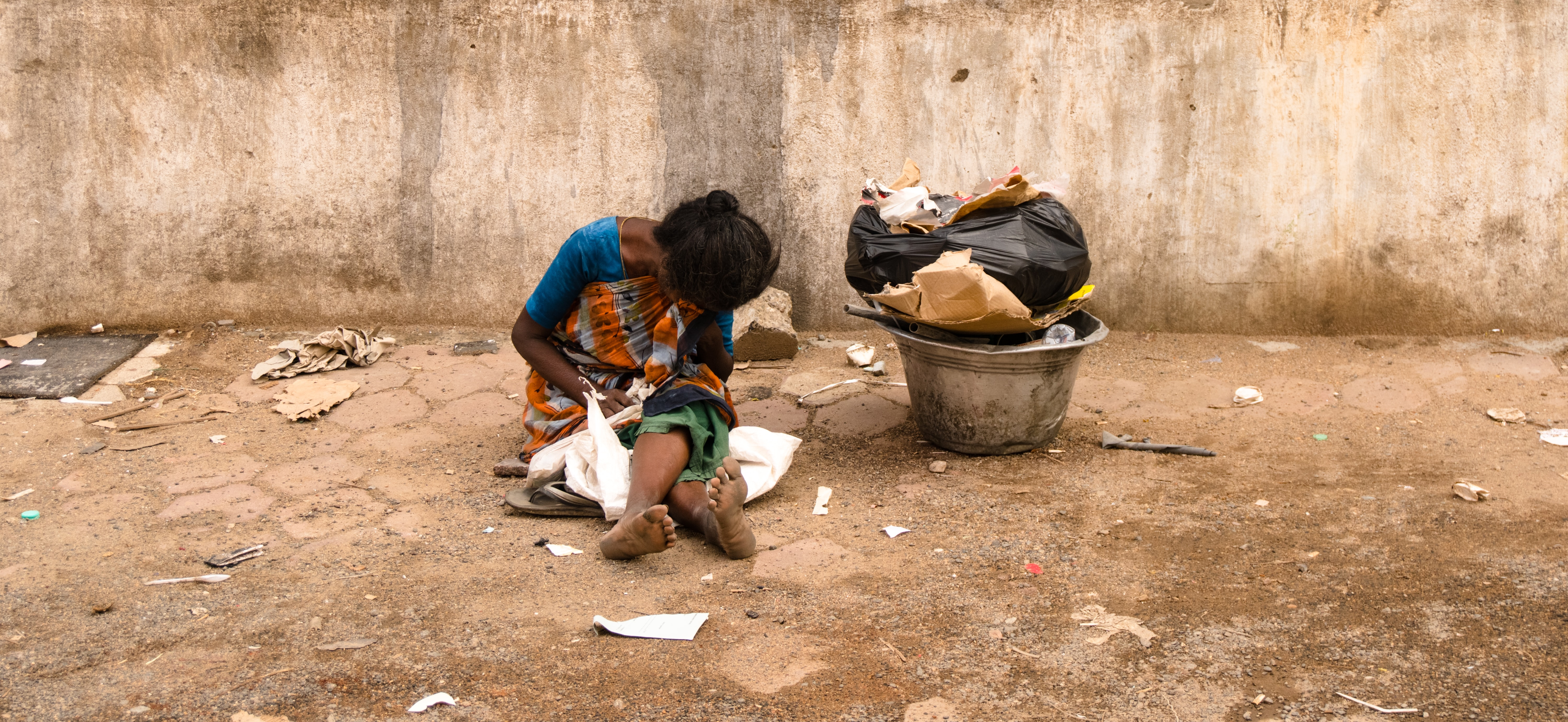 A woman sits against a wall on a dirty street aside a bucket