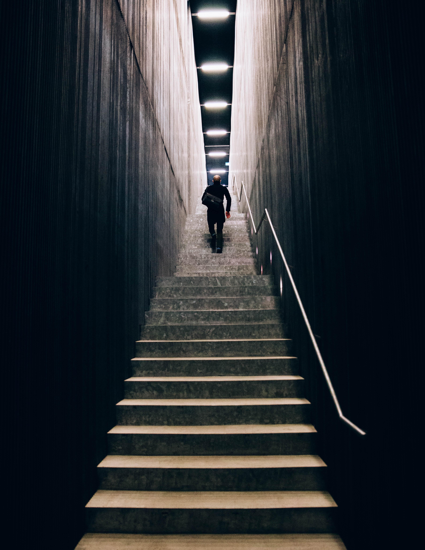 A lone man with a handbag climbing high stairs