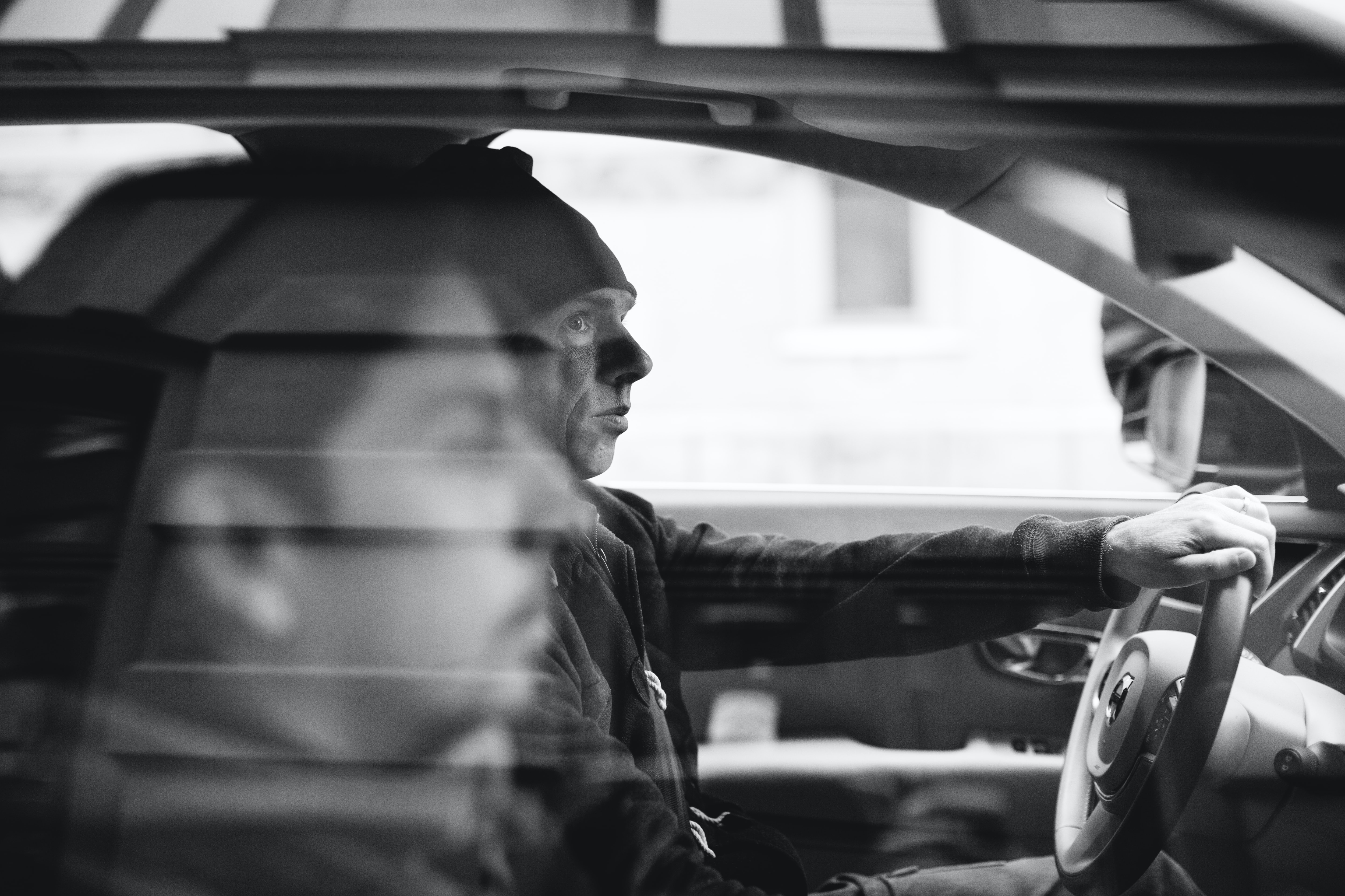 grayscale photo of two men riding on vehicle