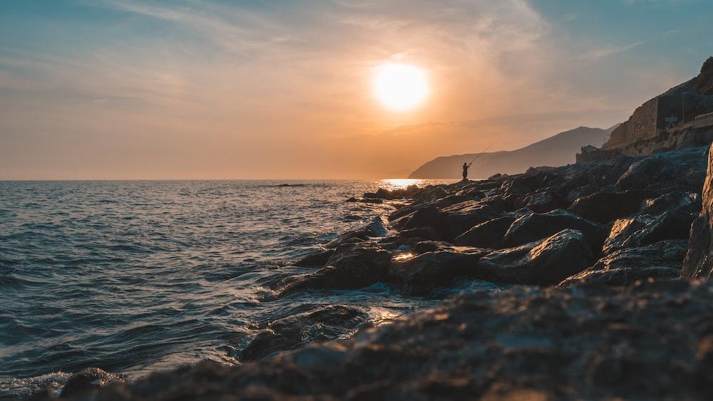 person standing on rock facing ocean during golden hour