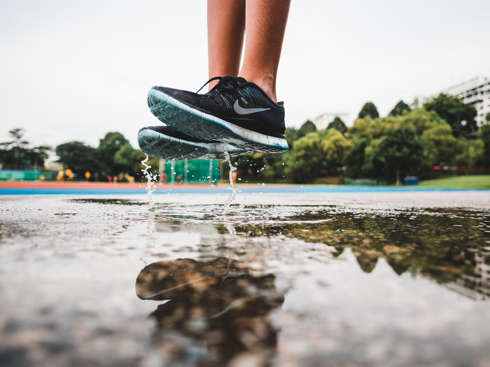 person wearing pair of gray-and-white Nike running shoes jumping on gray concrete floor with water during daytime