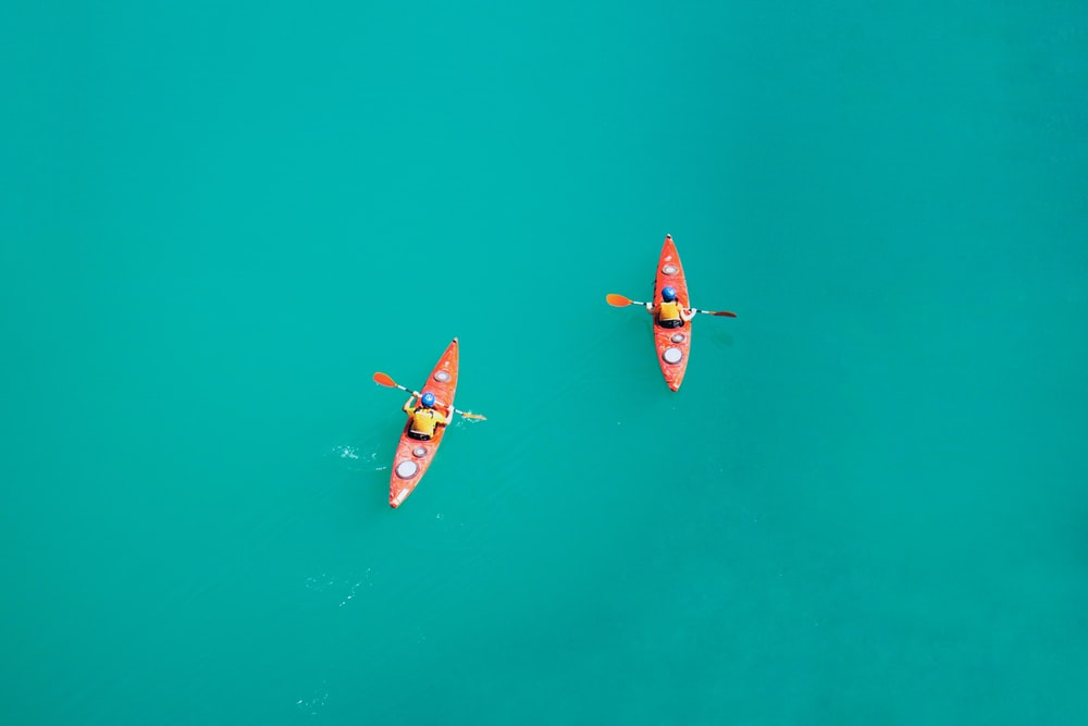 two person kayaking on open body of water