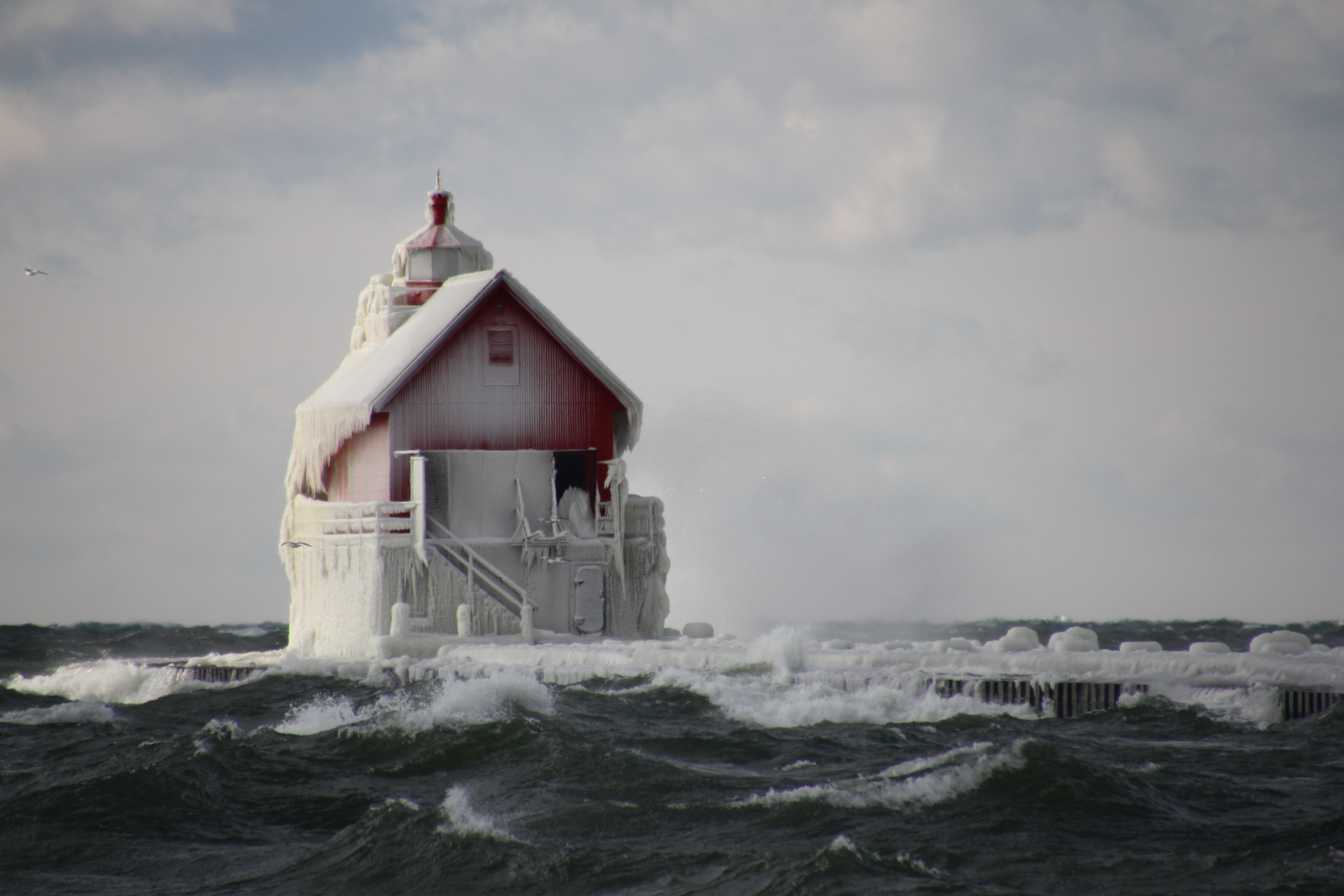 A small building surrounded by ocean waves and frozen snow