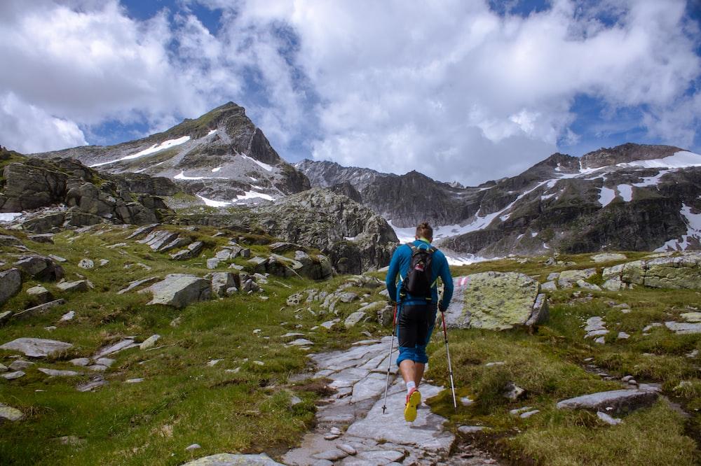 man running near rocky mountain during daytime