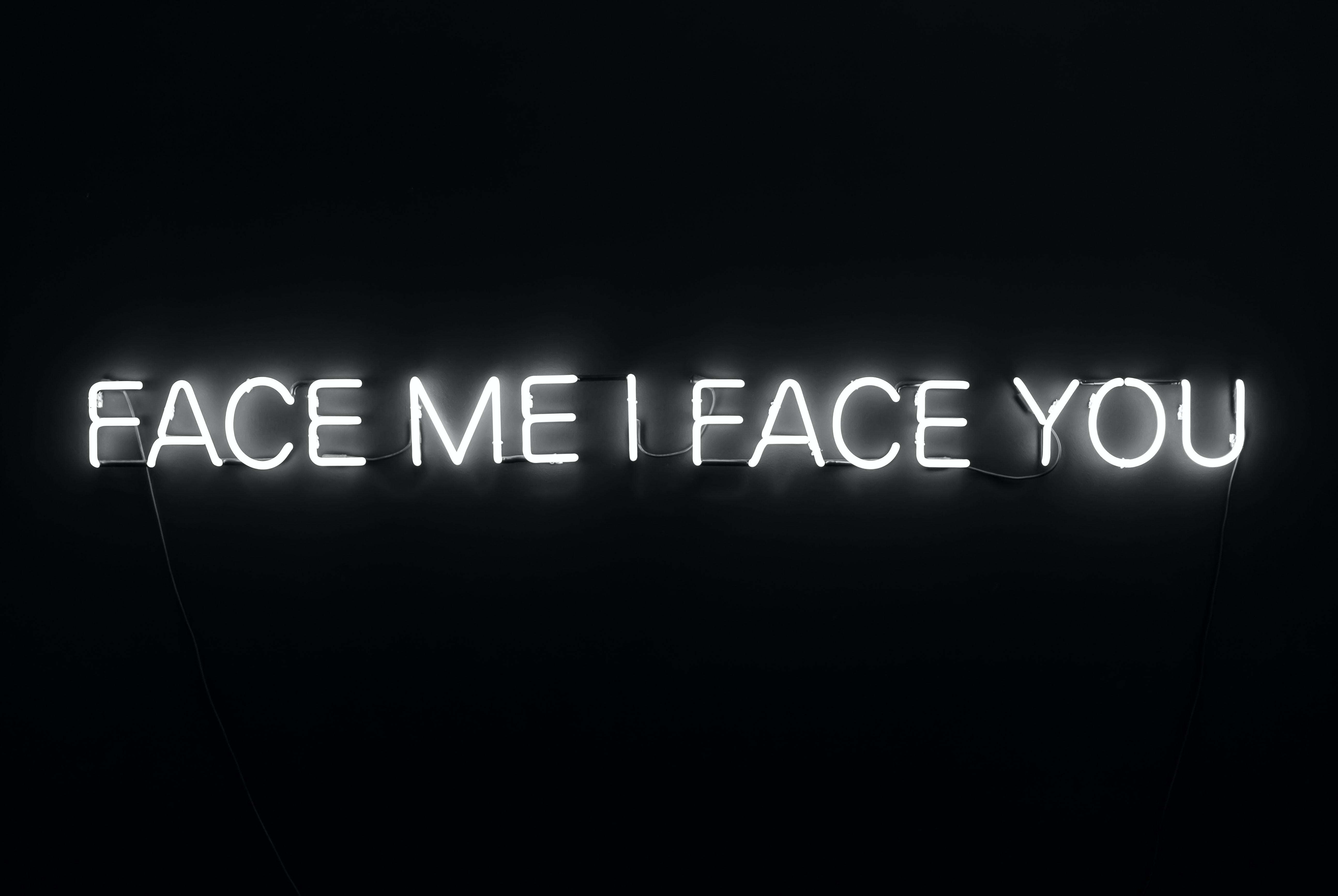 Face me I face you white neon sign at work on dark background, Phoenix Art Museum