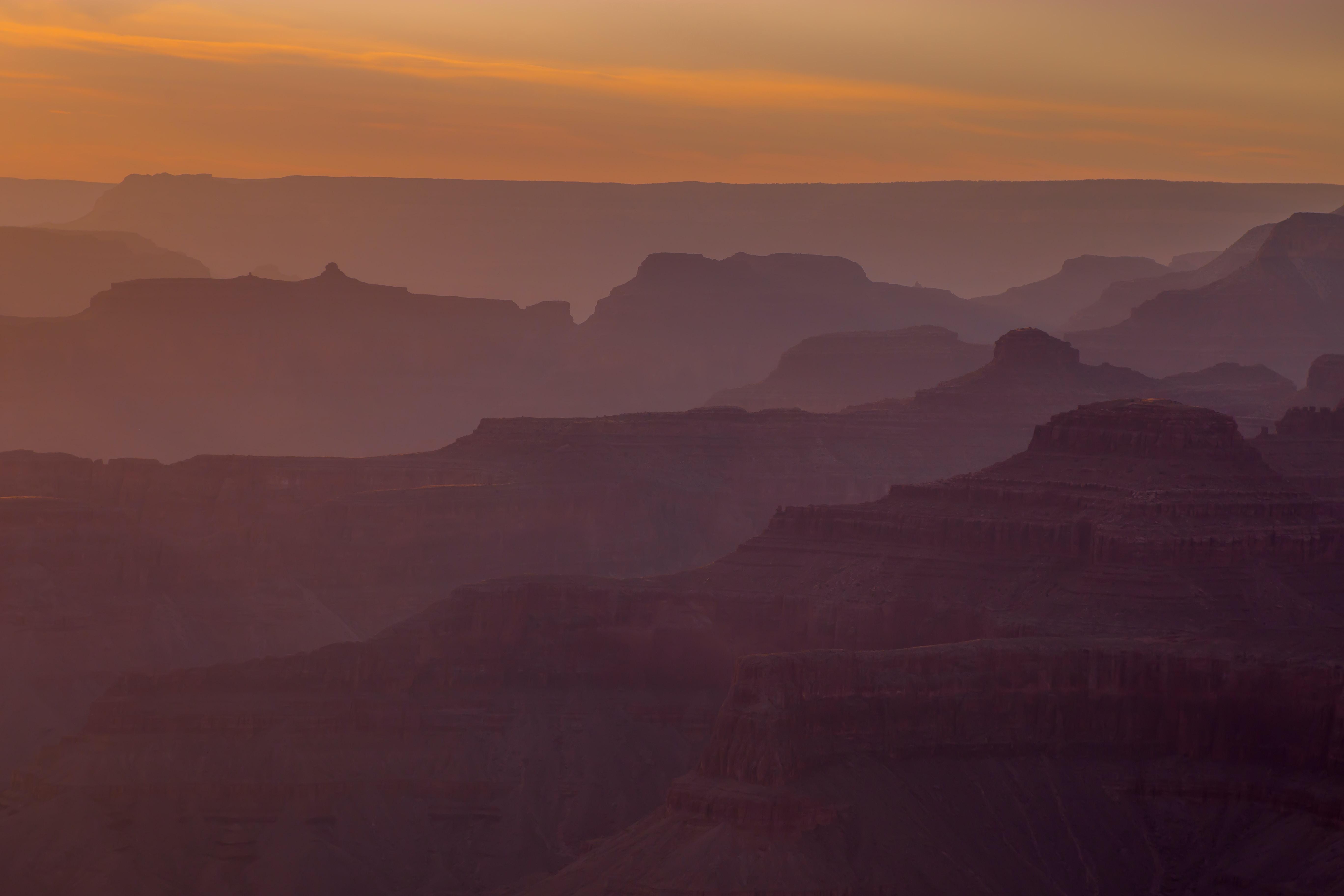 Hazy view of rock formations at Arizona's Grand Canyon National Park at dusk