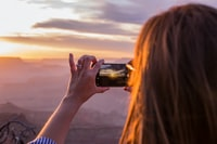 woman taking picture of orange sunset