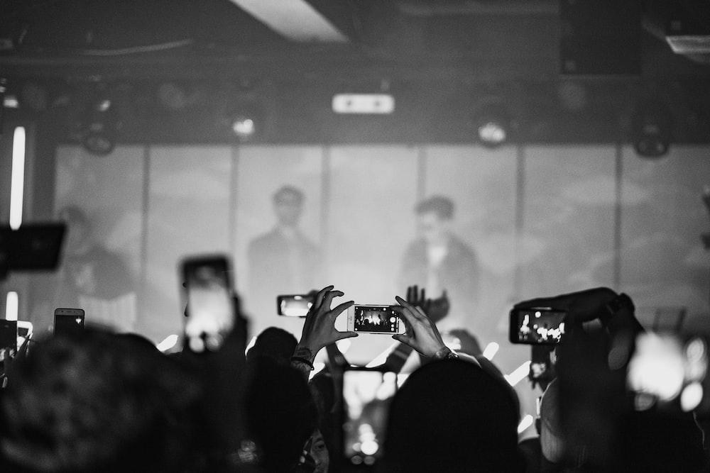 crowd taking photo of man wearing black sunglasses