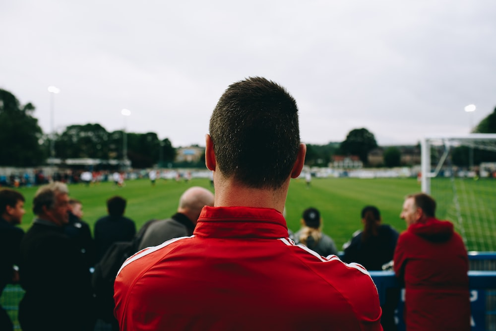 Man at the Guiseley Football Club watching the game and wearing a red jacket