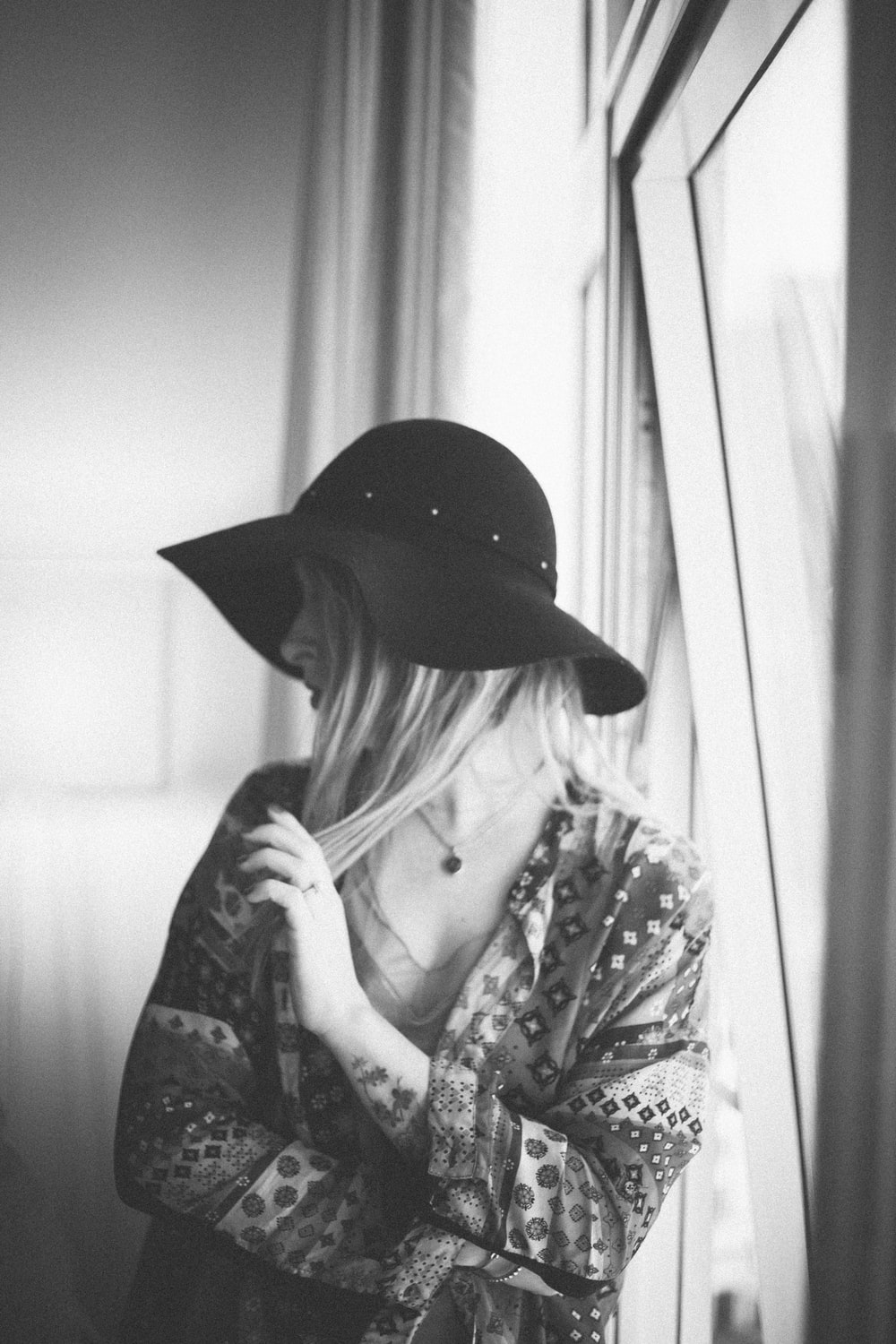 woman in black hat and white and black floral long sleeve shirt