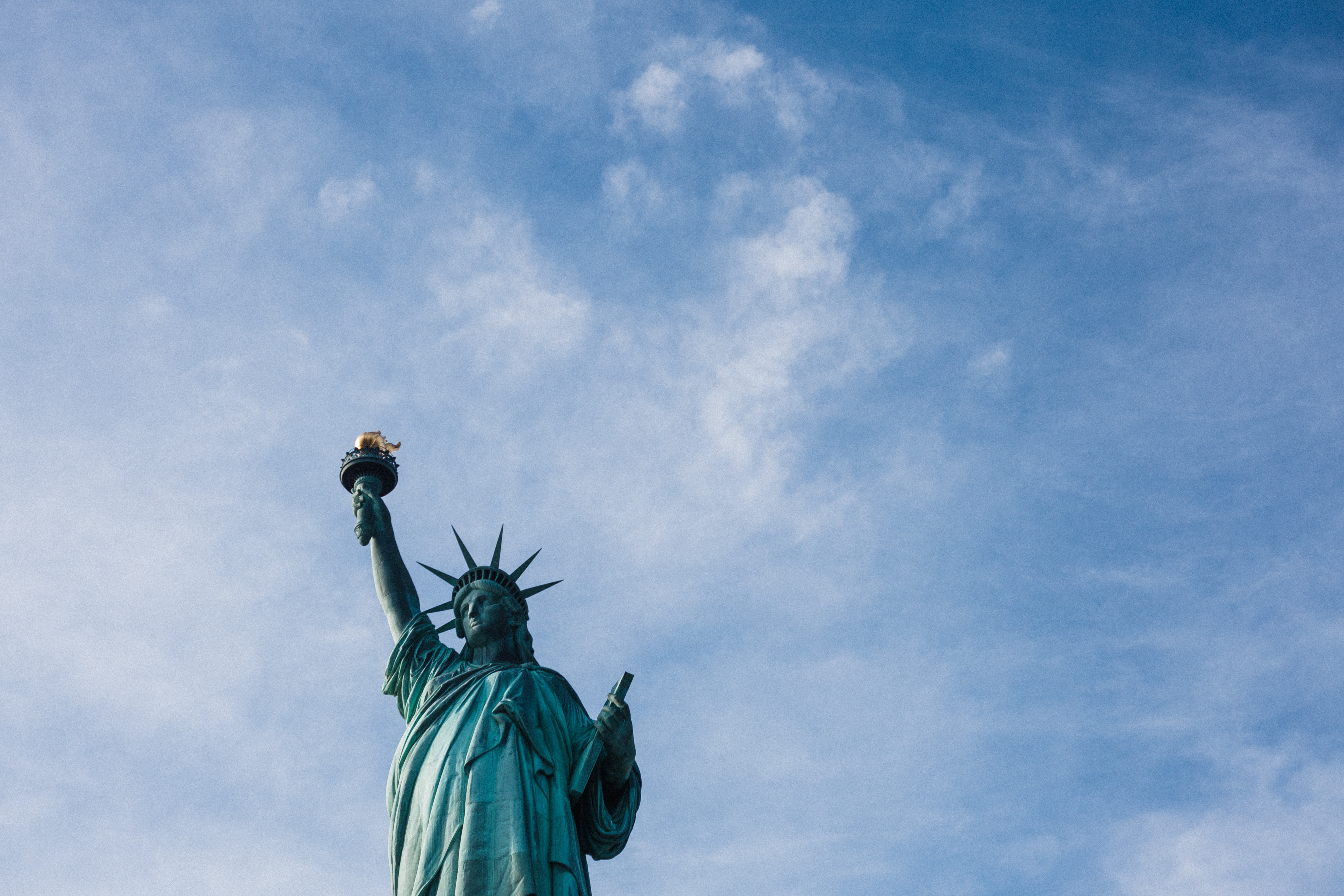 low angle photo of Statue of Liberty under blue and white cloudy daytime sky