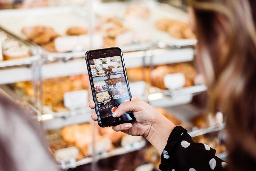 woman taking photo food display