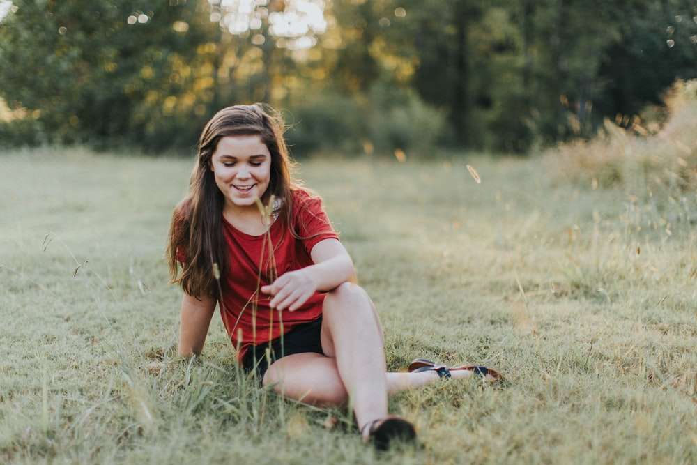 selective focus photo of woman sitting on the grass