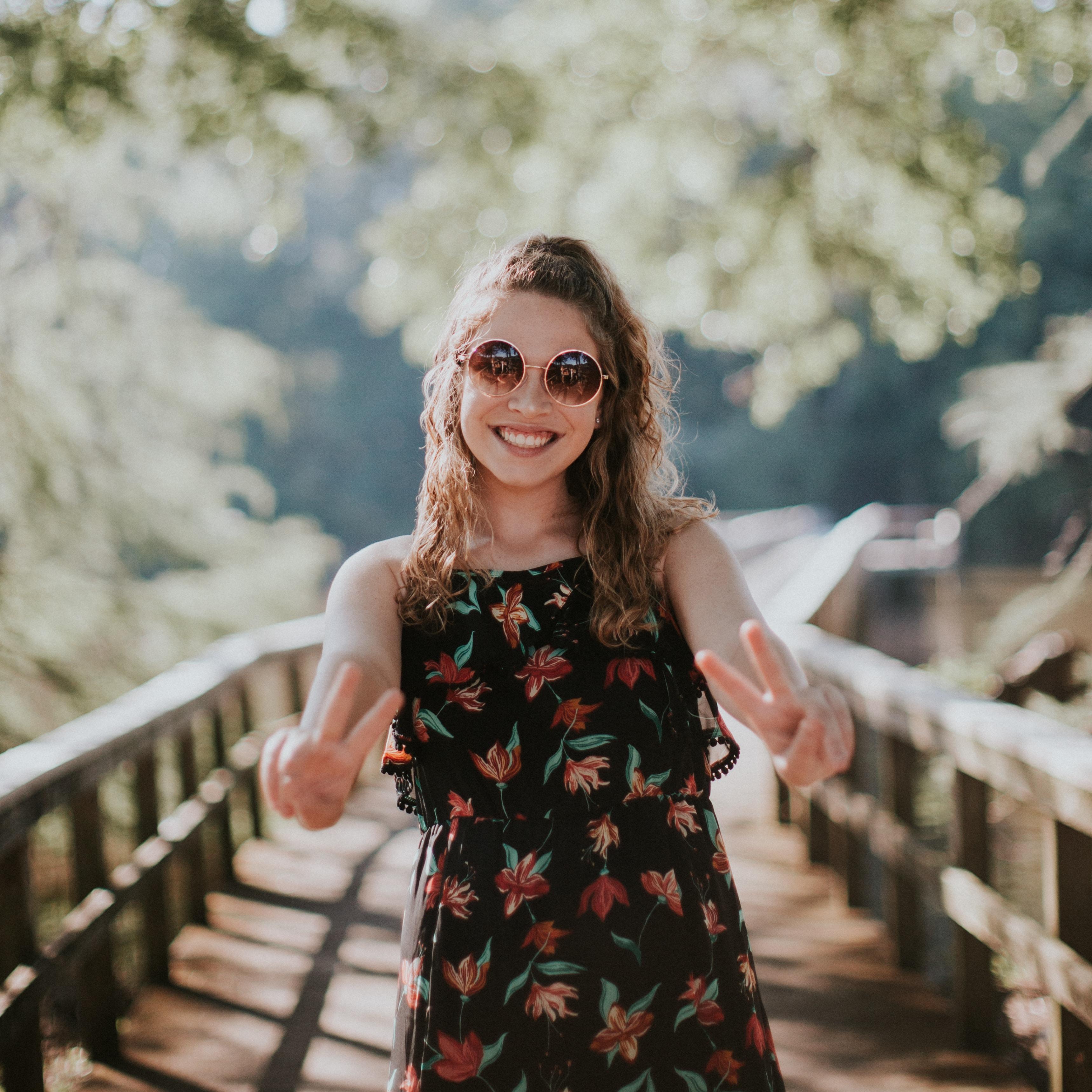 woman standing on wooden bridge