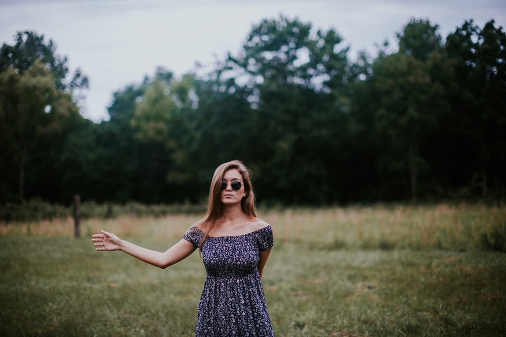 selective focus photo of woman standing on grass field
